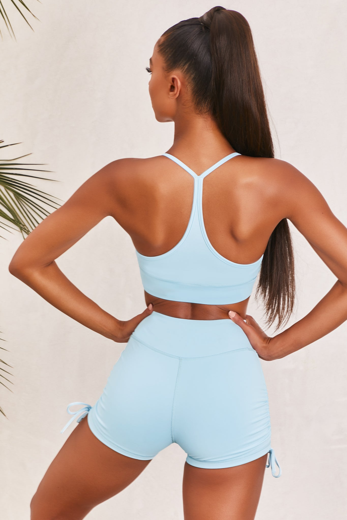 Plain ice blue slinky V neck sports bra with ruched centre and racer back. Image 3 of 6.