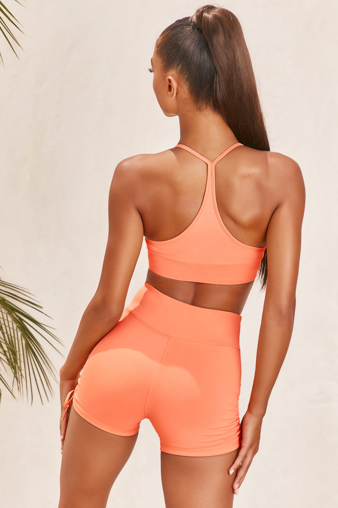Plain orange slinky V neck sports bra with ruched centre and racer back. Image 3 of 6.