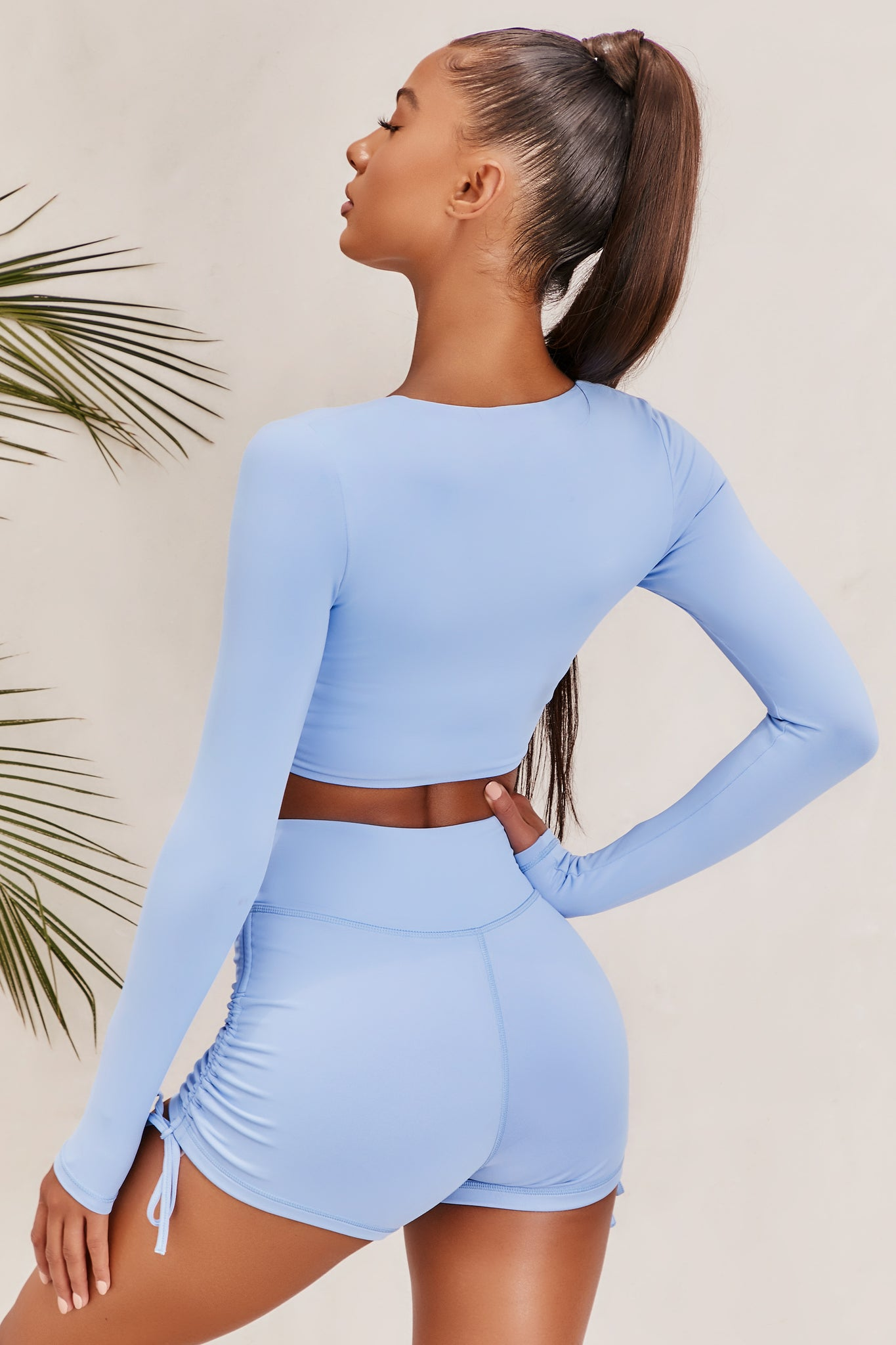 Plain baby blue slinky long sleeve crop top with plunge neckline and wrap front. Image of 3 of 6.