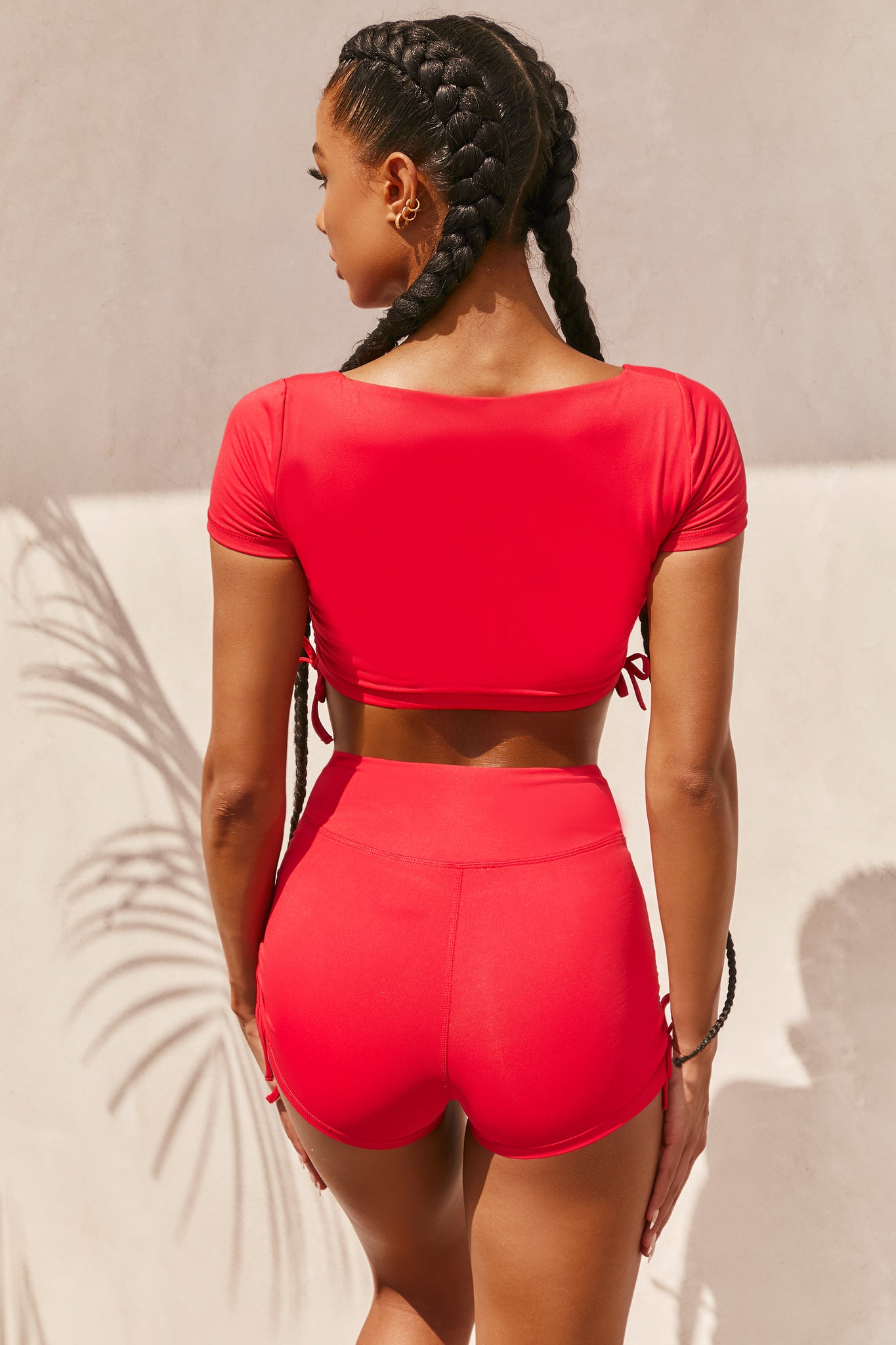 Plain red slinky short sleeve square neck crop top with ruched side seams and closed back. Image 3 of 6.