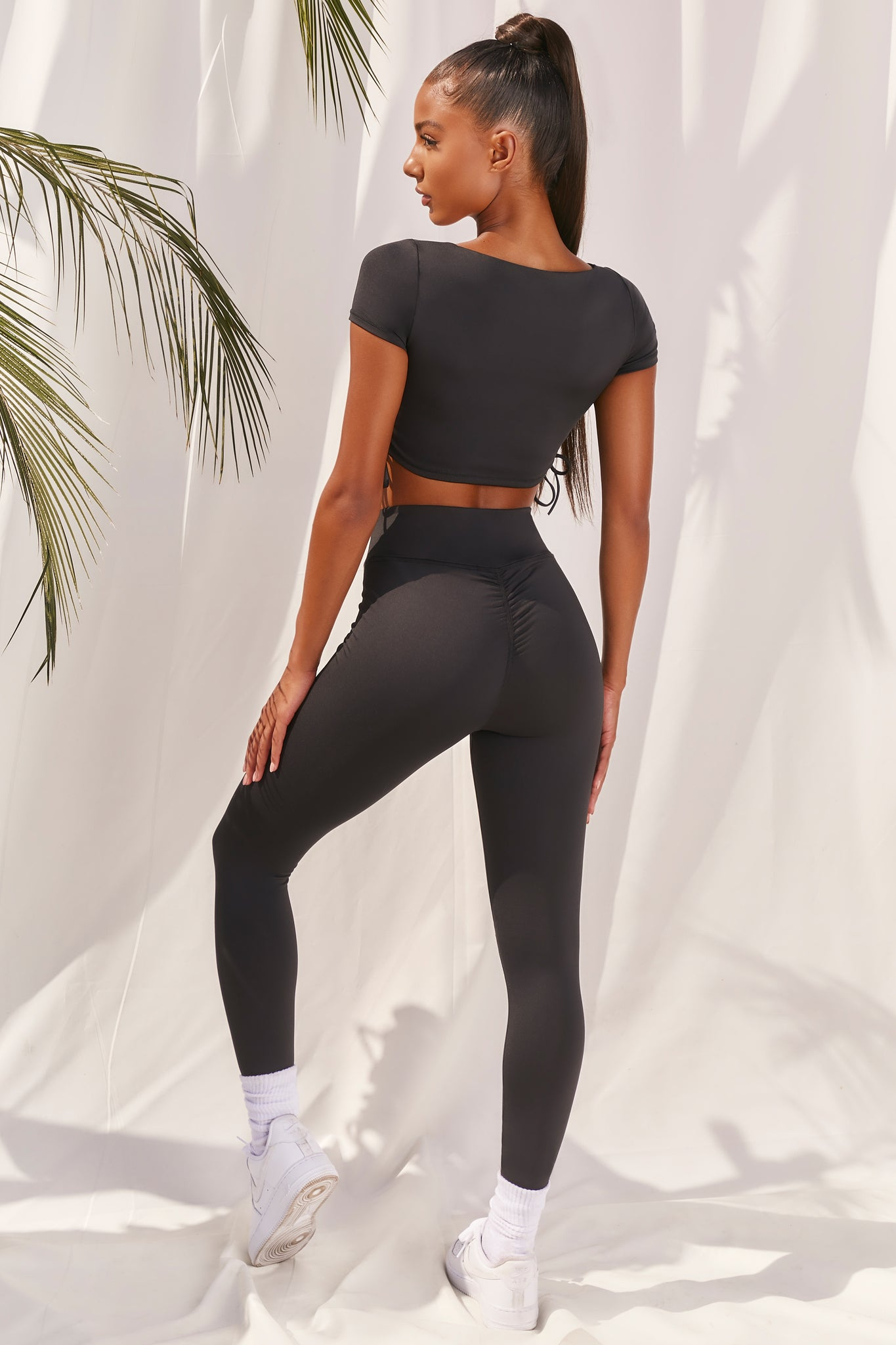 Plain black slinky high waisted full length gym leggings with rear ruched seam. Image 3 of 6.