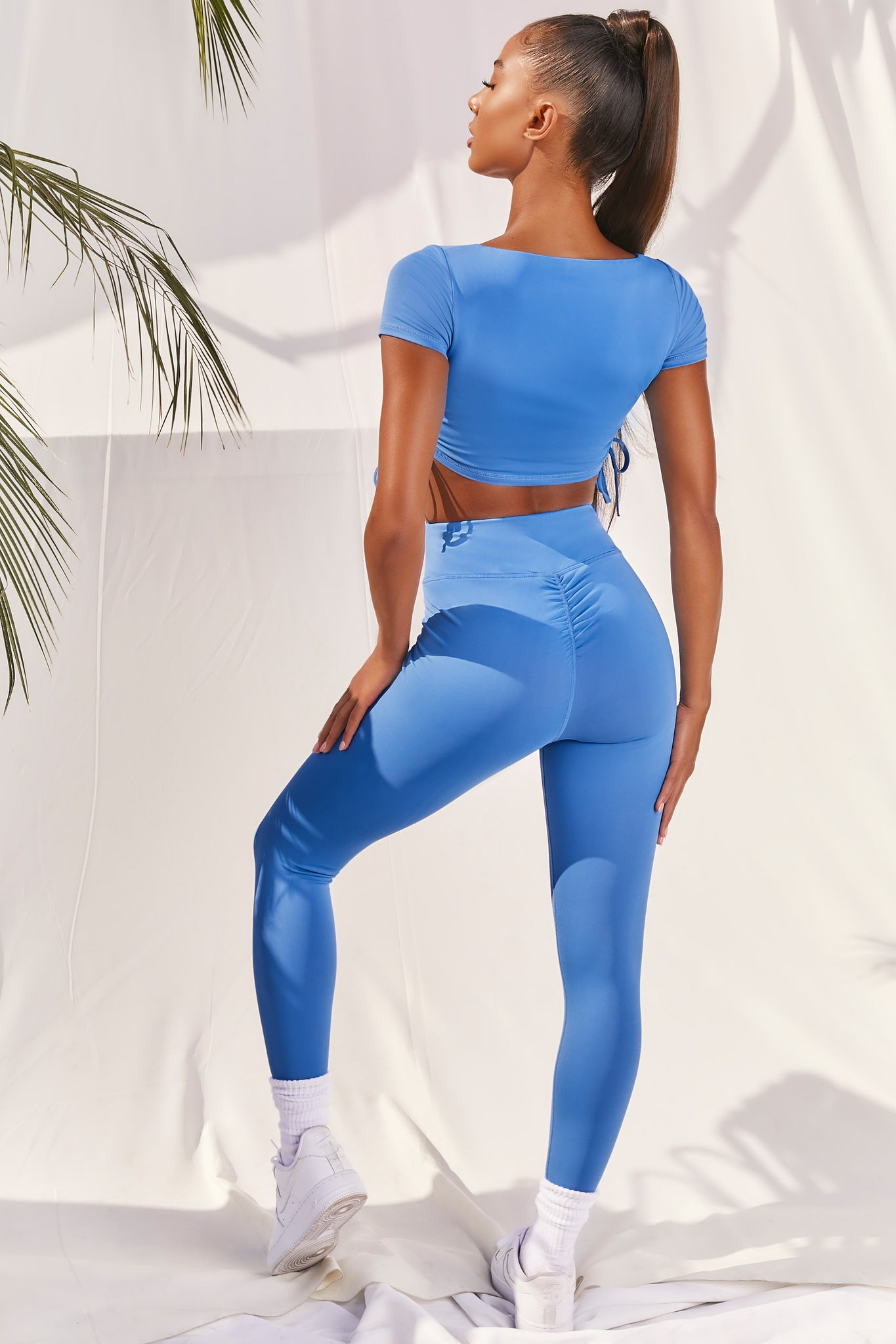 Plain bright blue slinky high waisted full length gym leggings with rear ruched seam. Image 3 of 6.