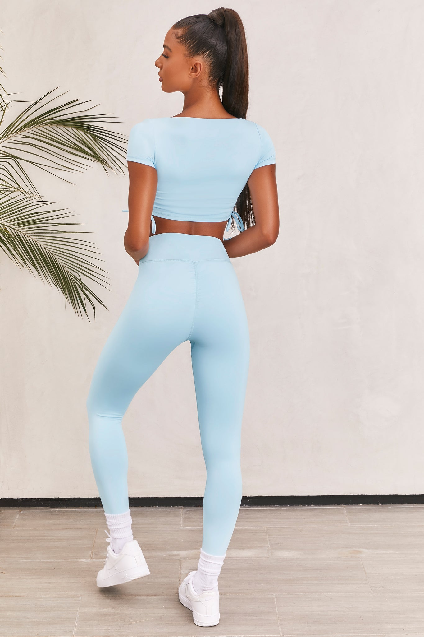 Plain ice blue slinky high waisted full length gym leggings with rear ruched seam. Image 3 of 6.