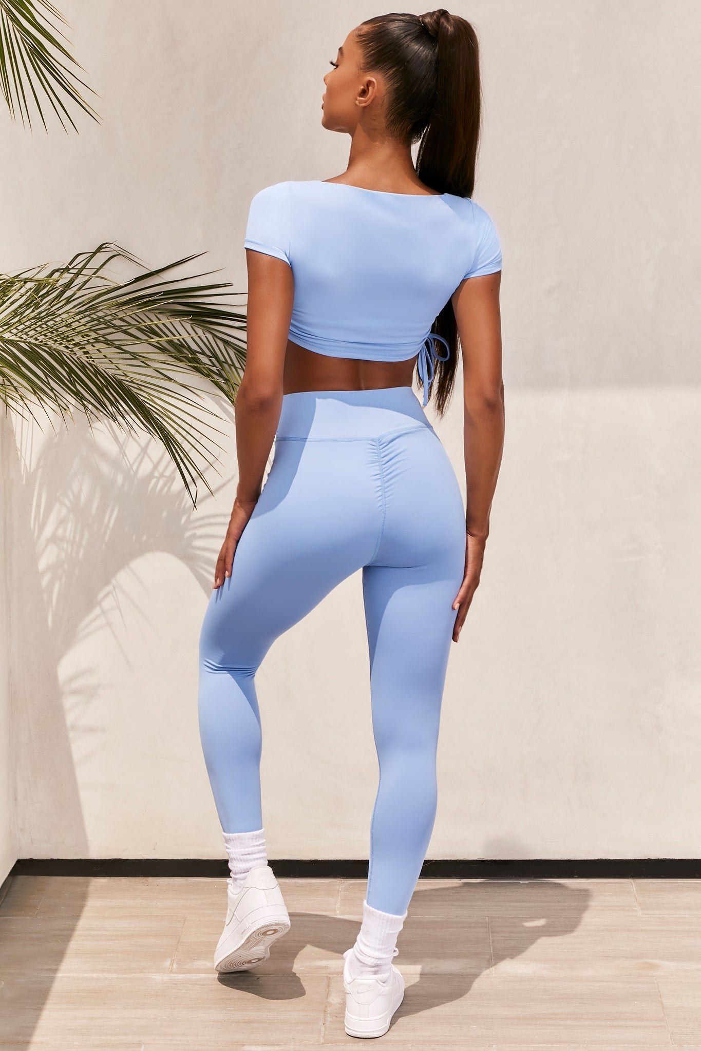 Plain baby blue slinky high waisted full length gym leggings with rear ruched seam. Image 3 of 6.