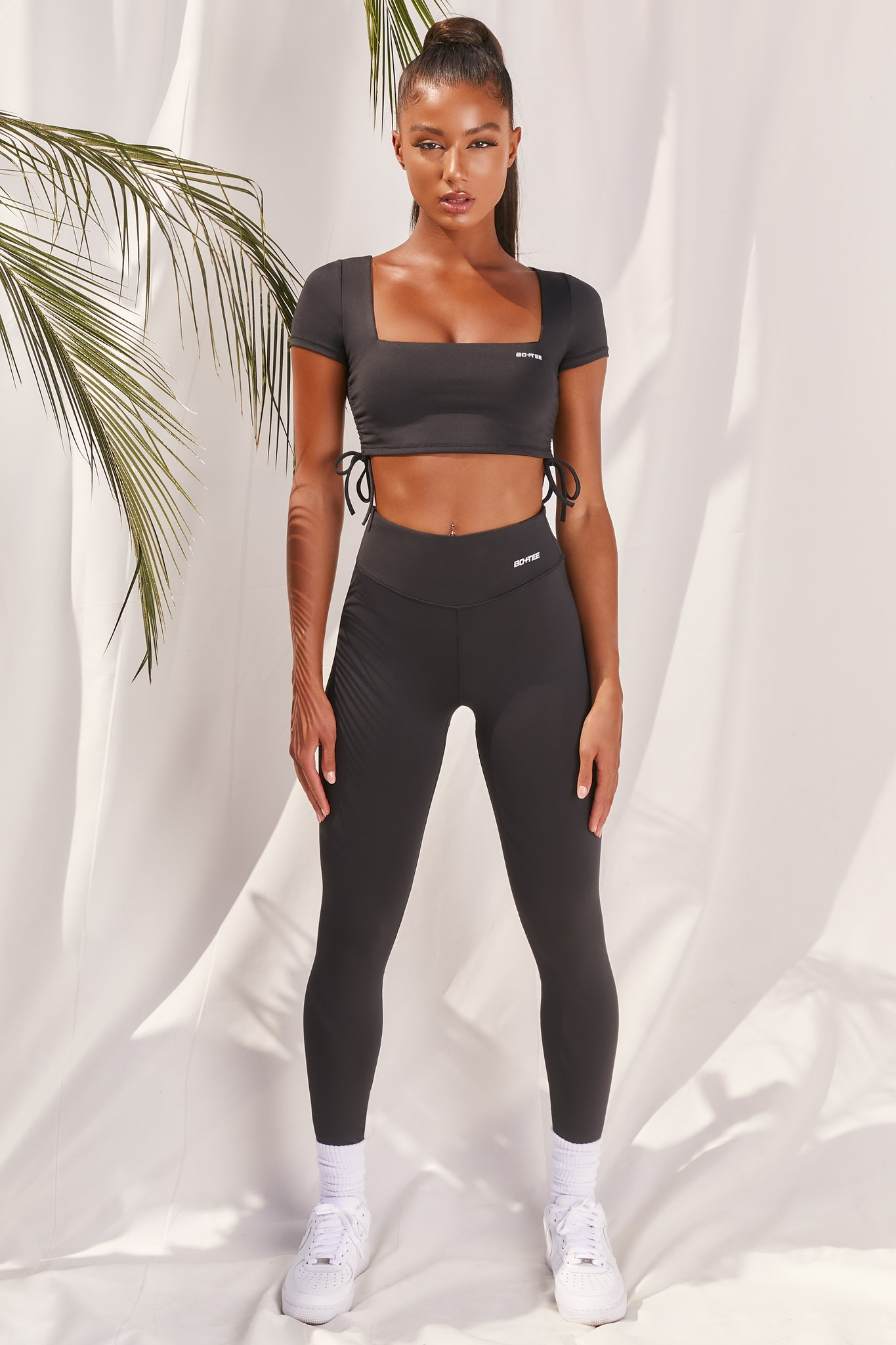 Plain black slinky high waisted full length gym leggings with rear ruched seam. Image 1 of 6.