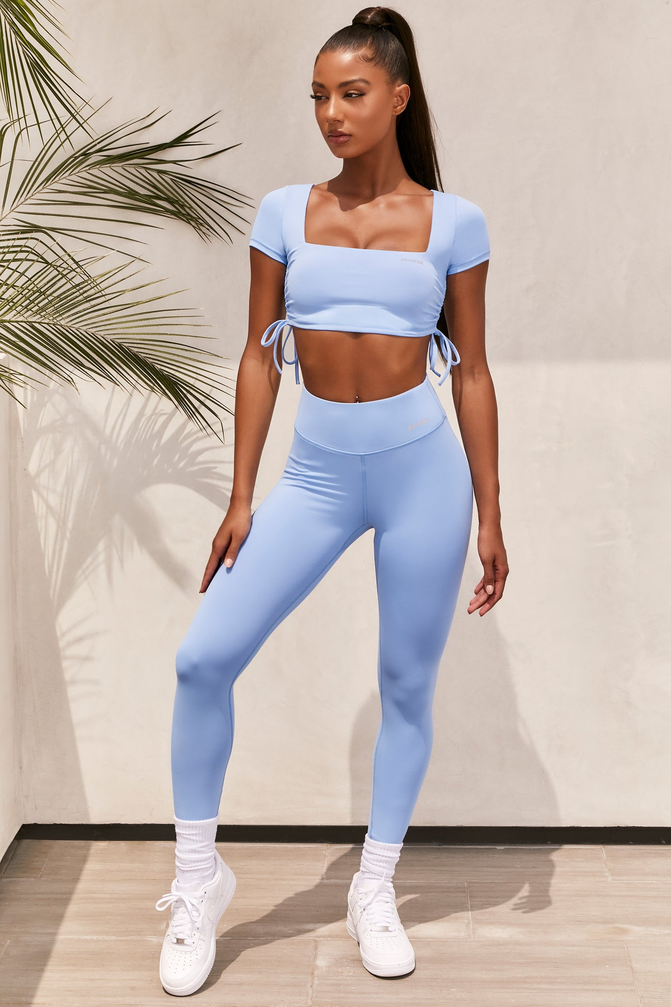 Plain baby blue slinky high waisted full length gym leggings with rear ruched seam. Image 1 of 6.