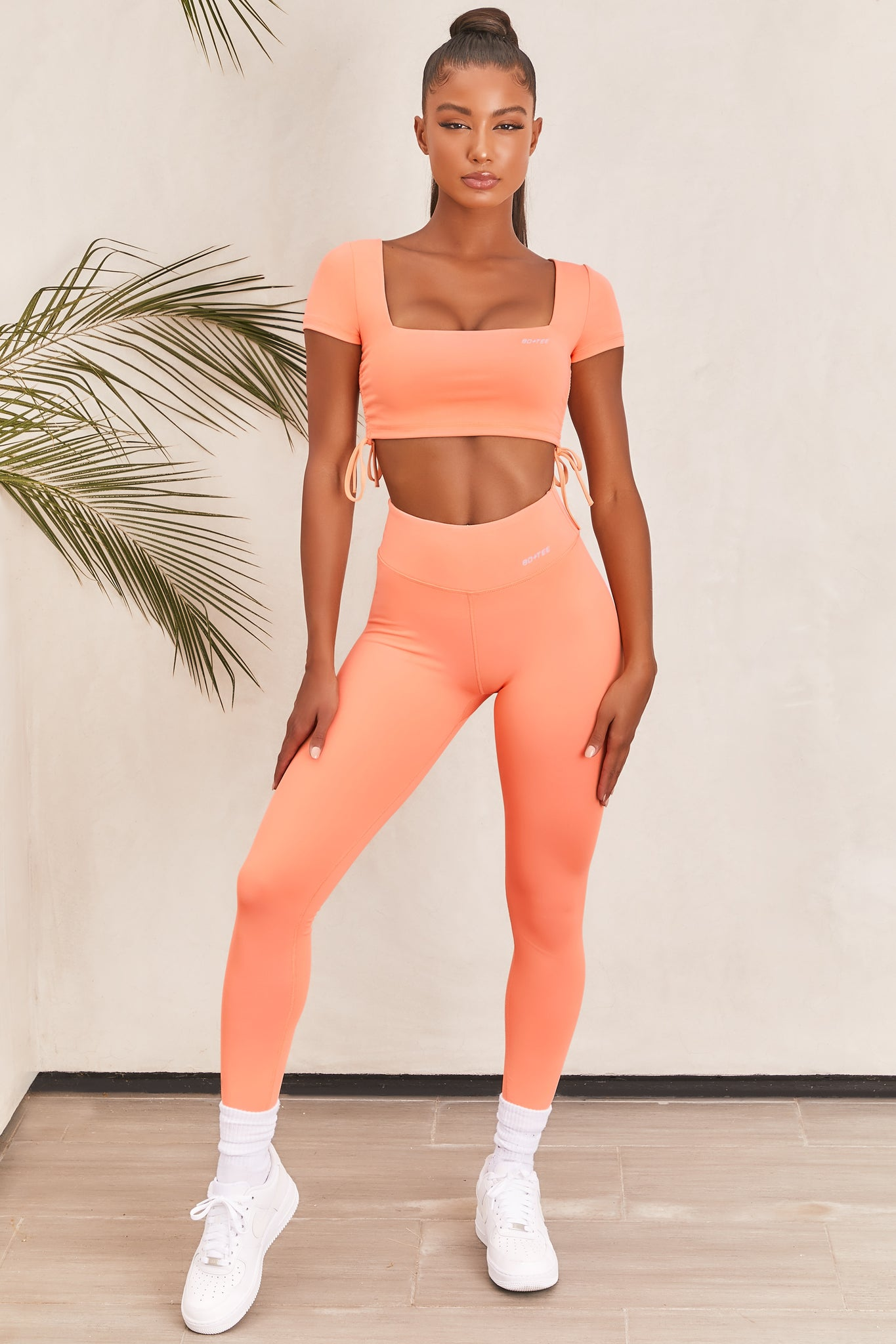 Plain orange slinky high waisted full length gym leggings with rear ruched seam. Image 1 of 6.