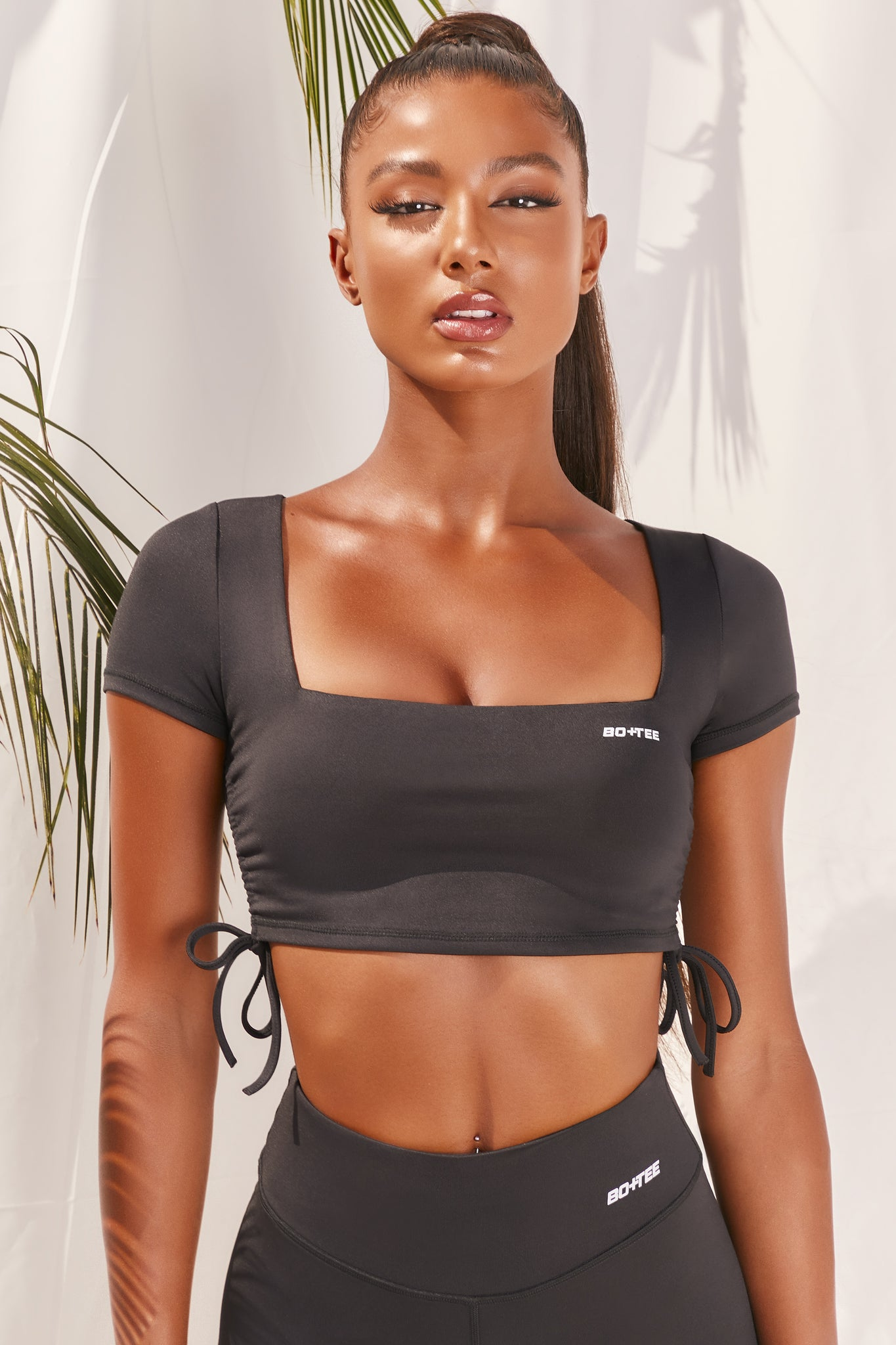 Plain black slinky short sleeve square neck crop top with ruched side seams and closed back. Image 1 of 6.