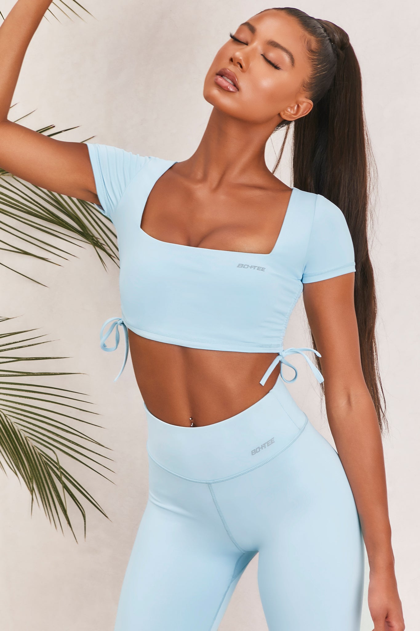 Plain ice blue slinky short sleeve square neck crop top with ruched side seams and closed back. Image 5 of 6.