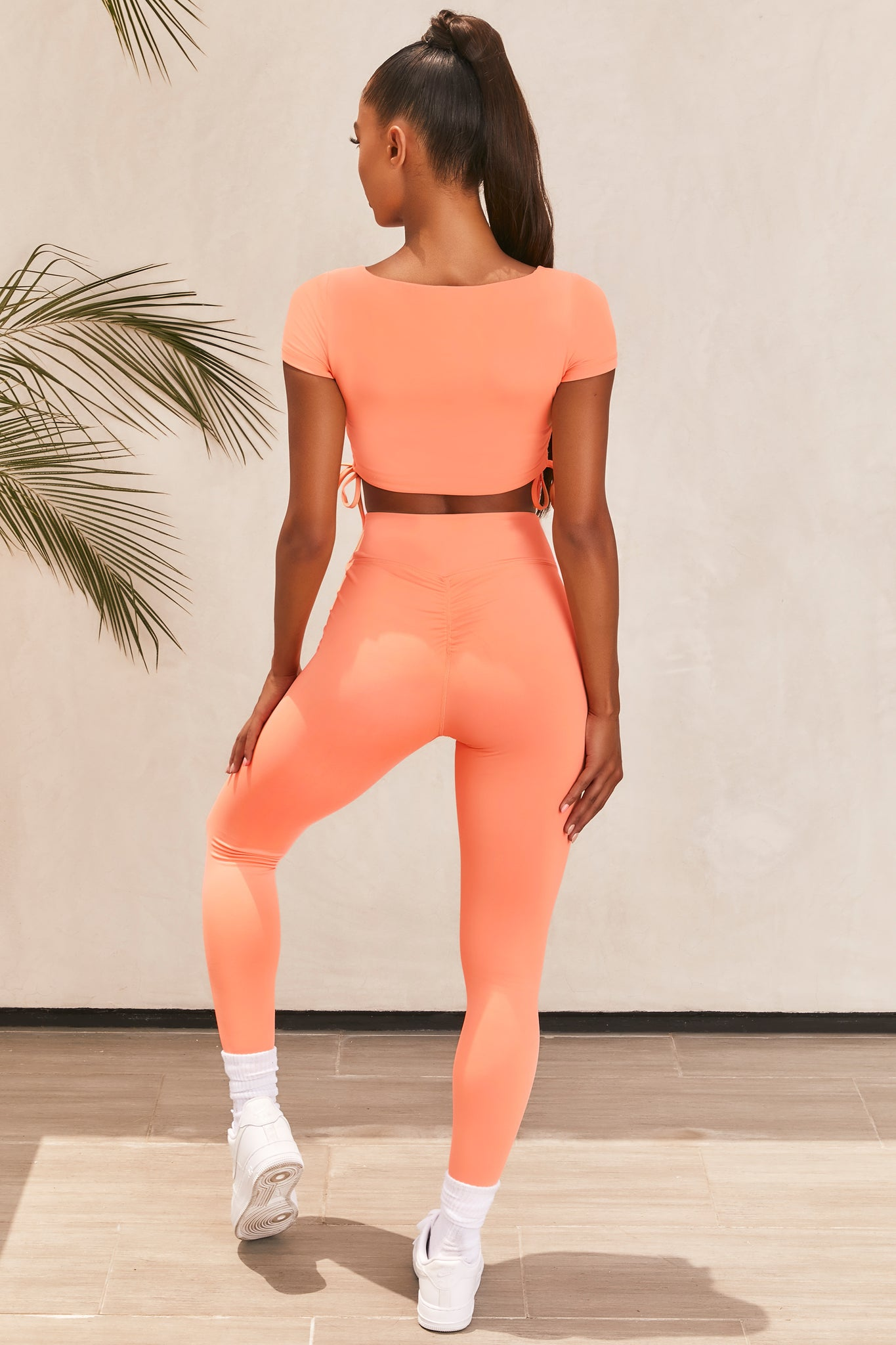 Plain orange slinky short sleeve square neck crop top with ruched side seams and closed back. Image 3 of 6.