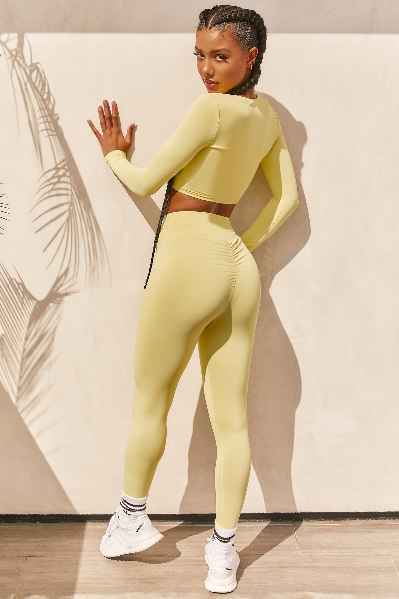Plain yellow slinky high waisted full length gym leggings with rear ruched seam. Image 3 of 6.