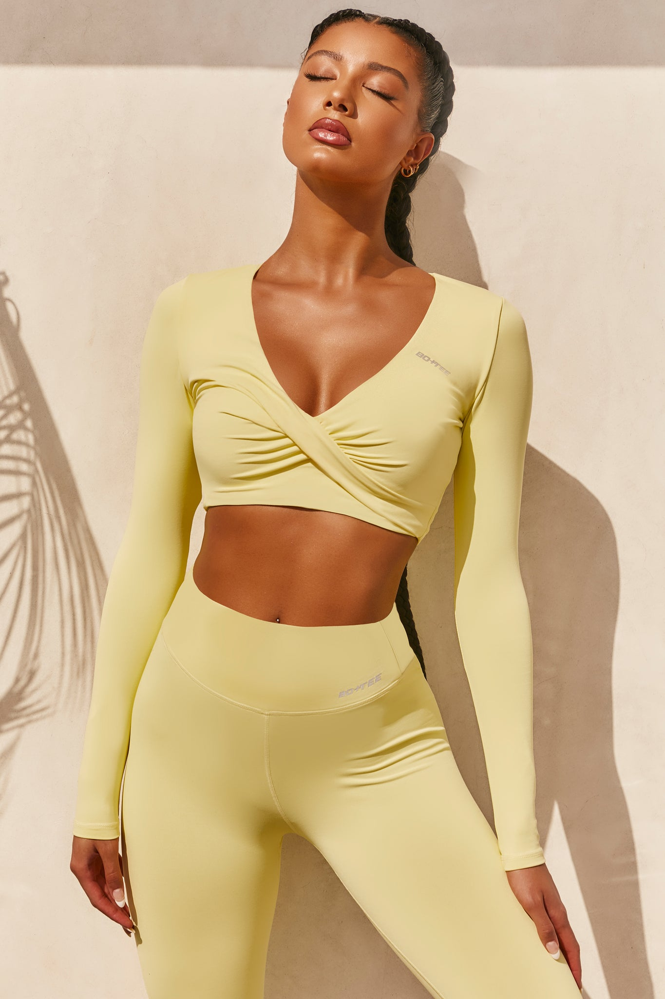 Plain yellow slinky long sleeve crop top with plunge neckline and wrap front. Image of 1 of 6.