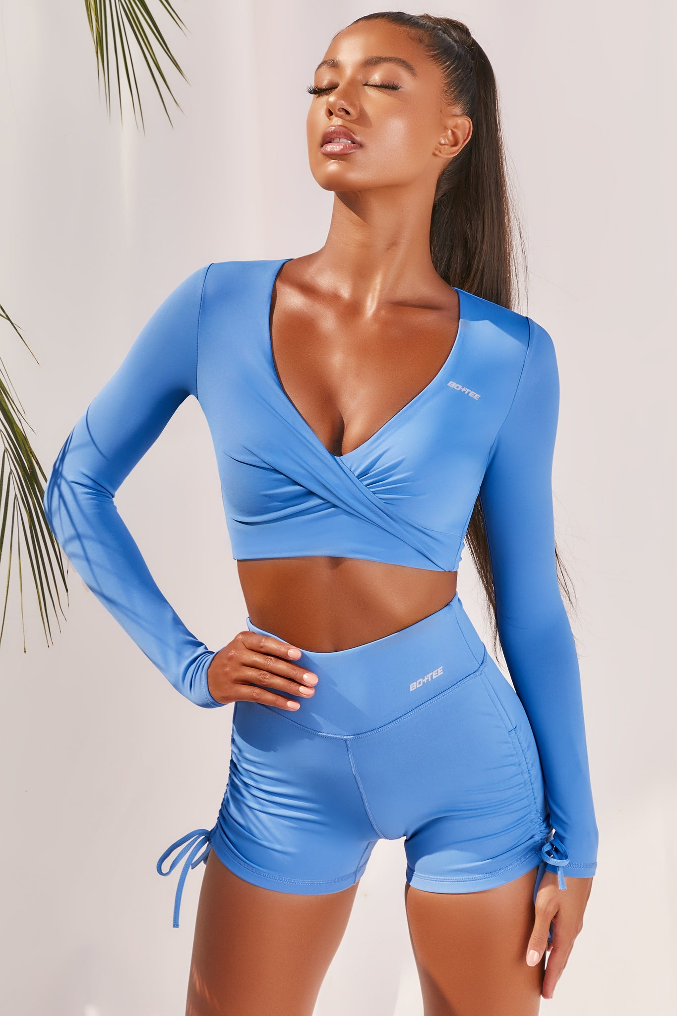 Plain bright blue slinky long sleeve crop top with plunge neckline and wrap front. Image of 6 of 6.