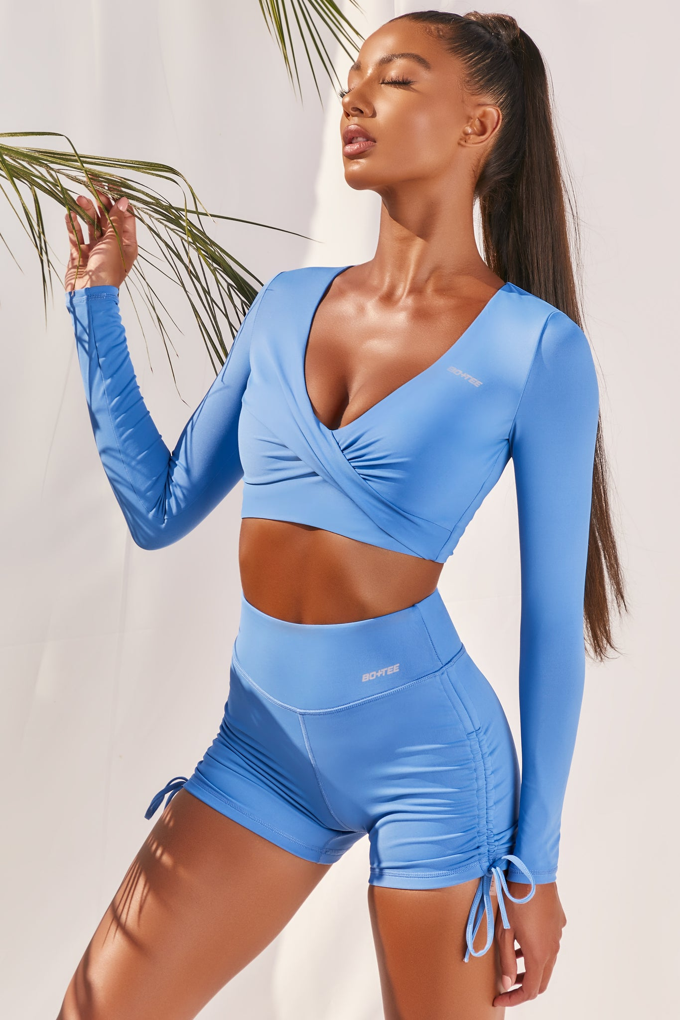 Plain bright blue slinky long sleeve crop top with plunge neckline and wrap front. Image of 2 of 6.