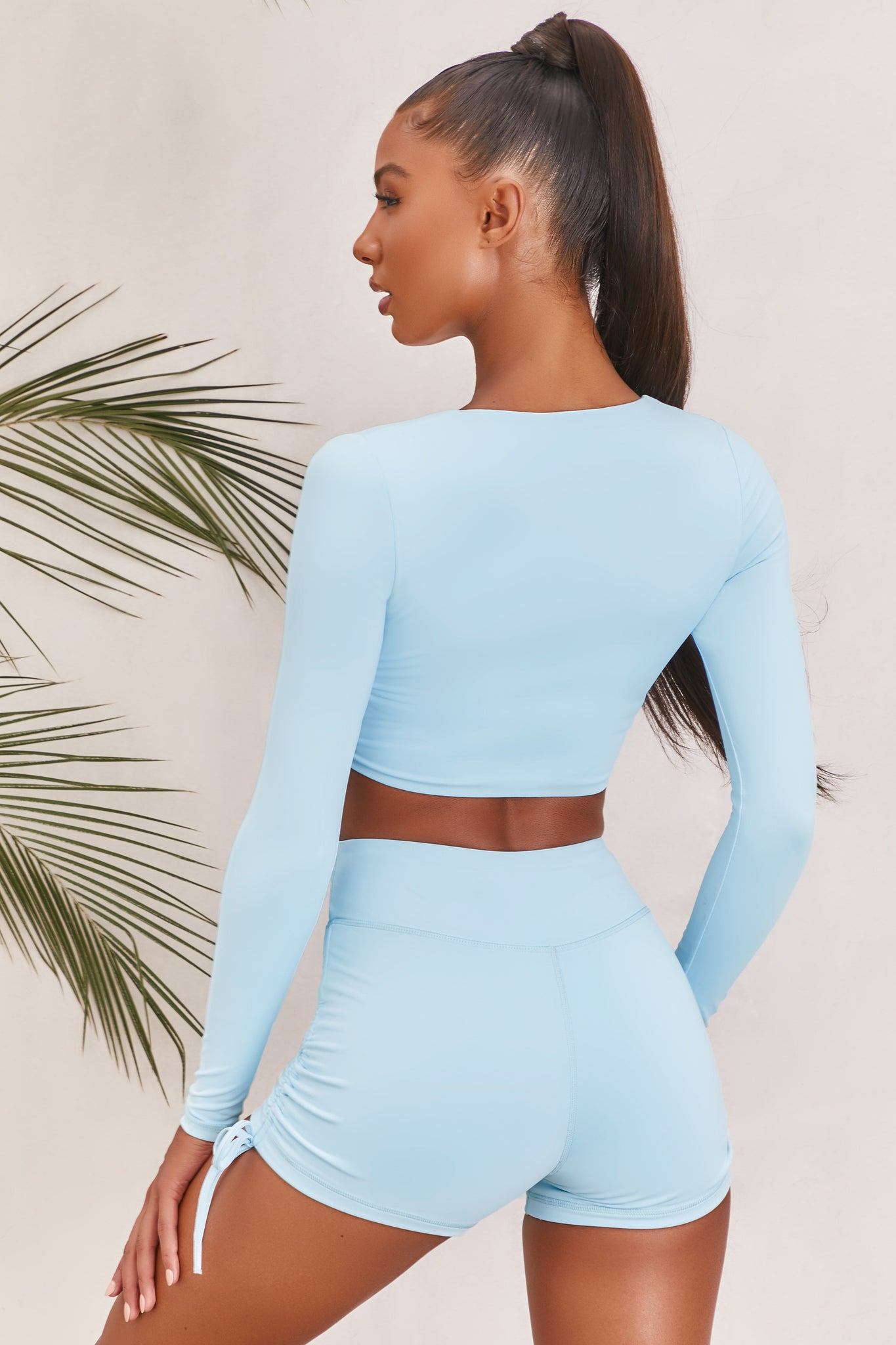 Plain ice blue slinky long sleeve crop top with plunge neckline and wrap front. Image of 3 of 6.