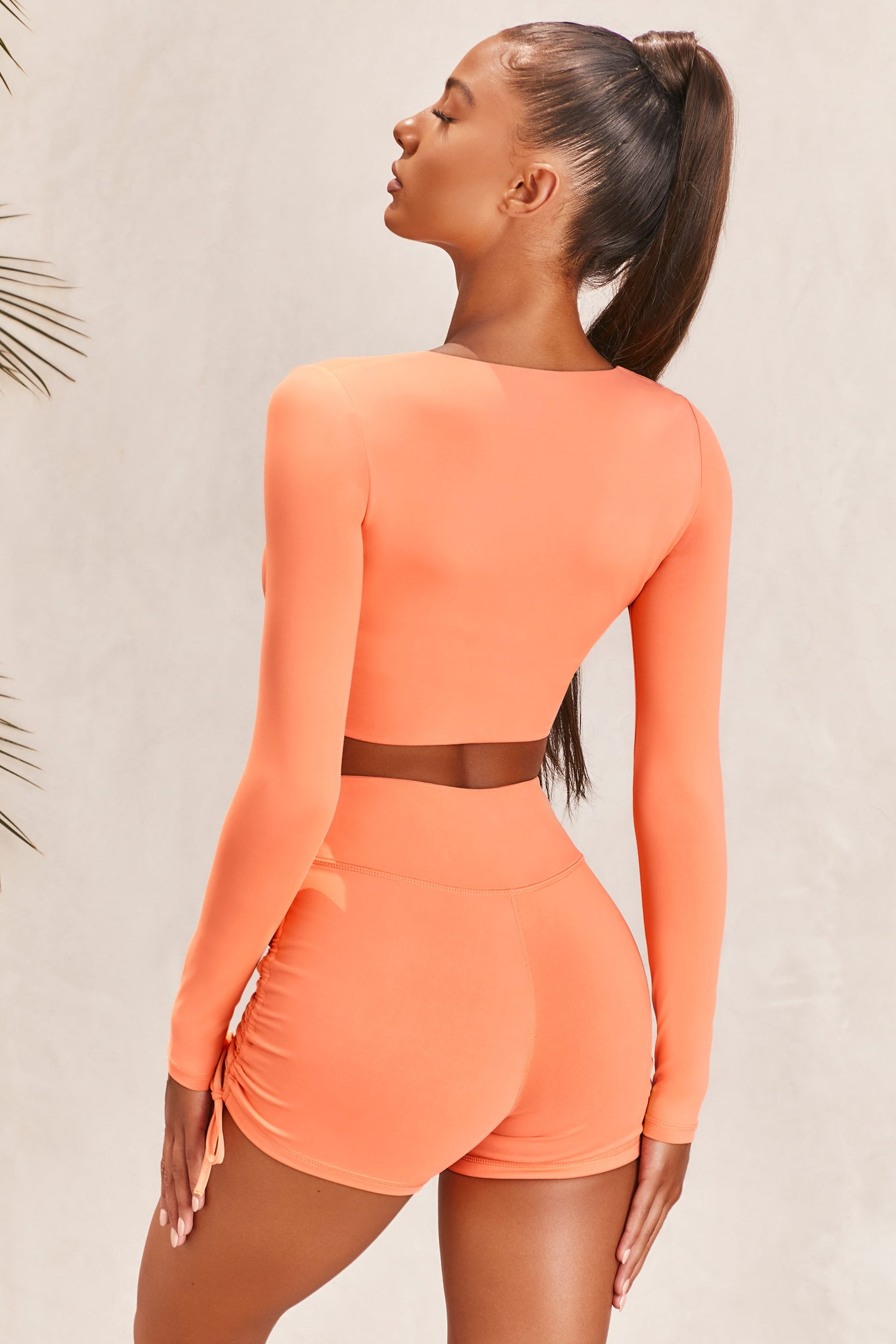 Plain orange slinky long sleeve crop top with plunge neckline and wrap front. Image of 3 of 6.