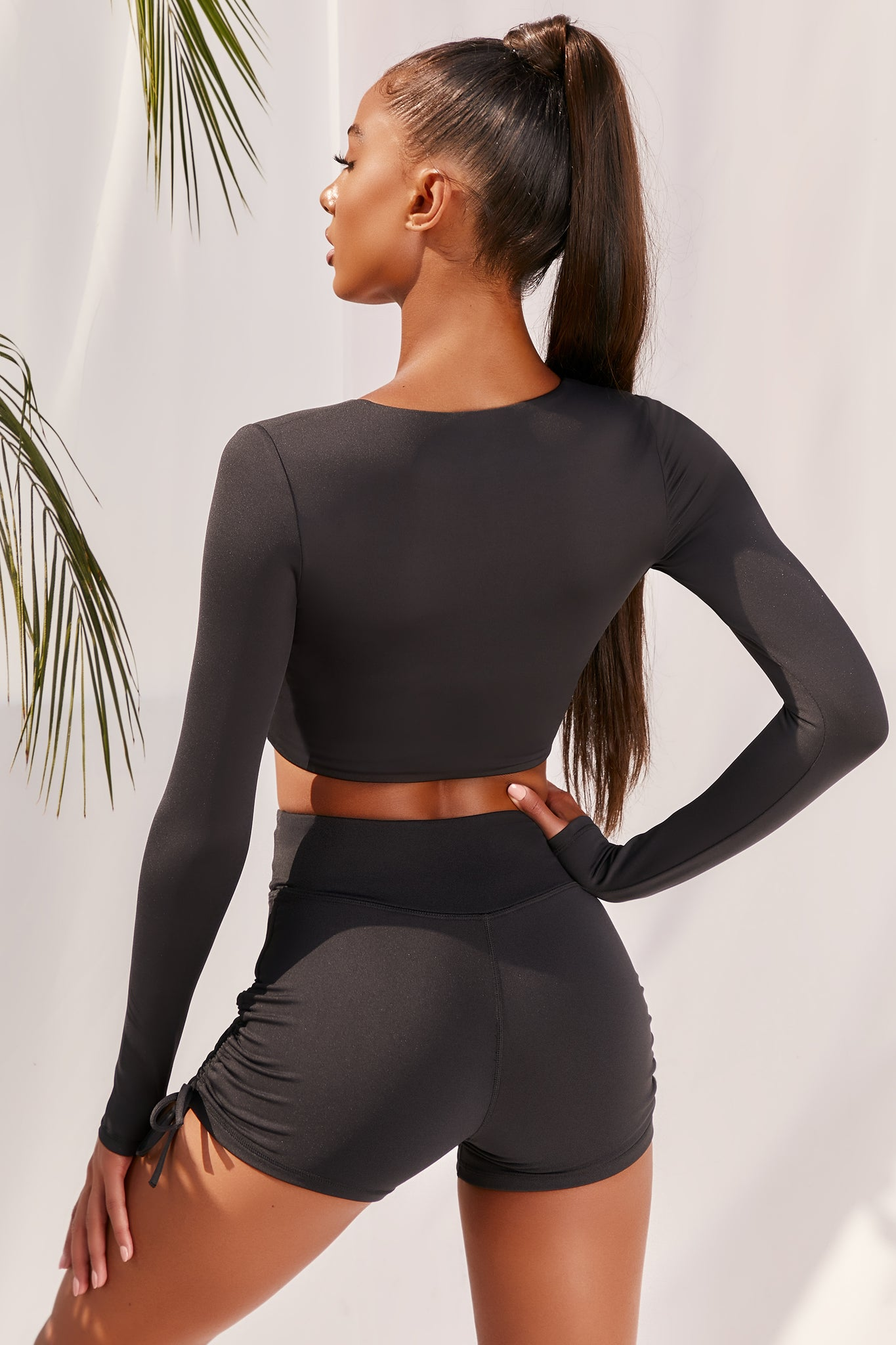 Plain black slinky long sleeve crop top with plunge neckline and wrap front. Image of 3 of 6.