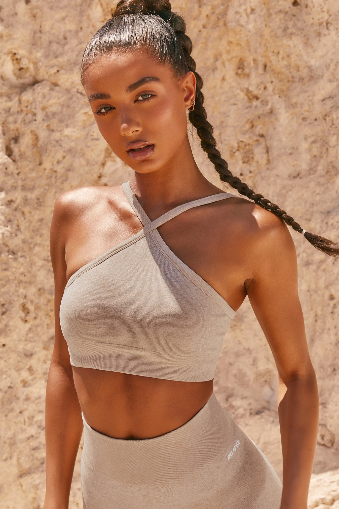 Plain sand seamless sports bra with cross high-neck adjustable straps and ribbed underband. Image 1 of 6.