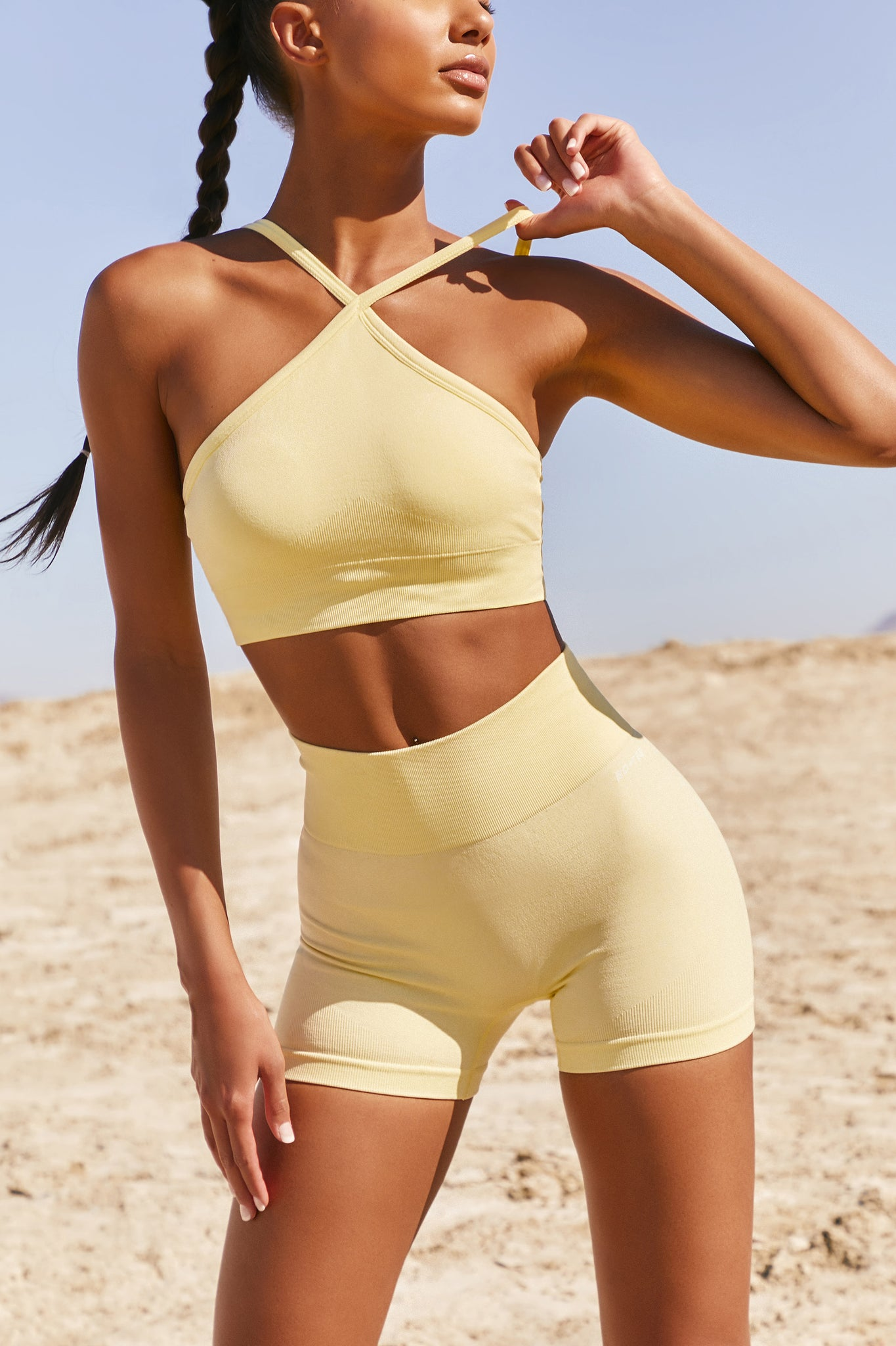 Plain lemon seamless sports bra with cross high-neck adjustable straps and ribbed underband. Image 1 of 6.