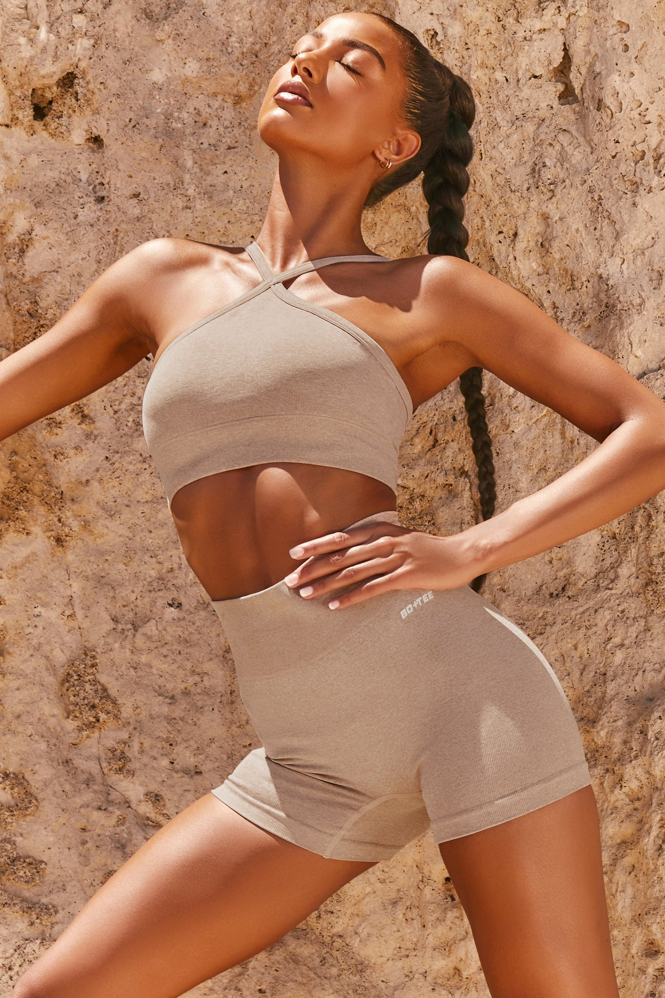 Plain sand seamless sports bra with cross high-neck adjustable straps and ribbed underband. Image 6 of 6.