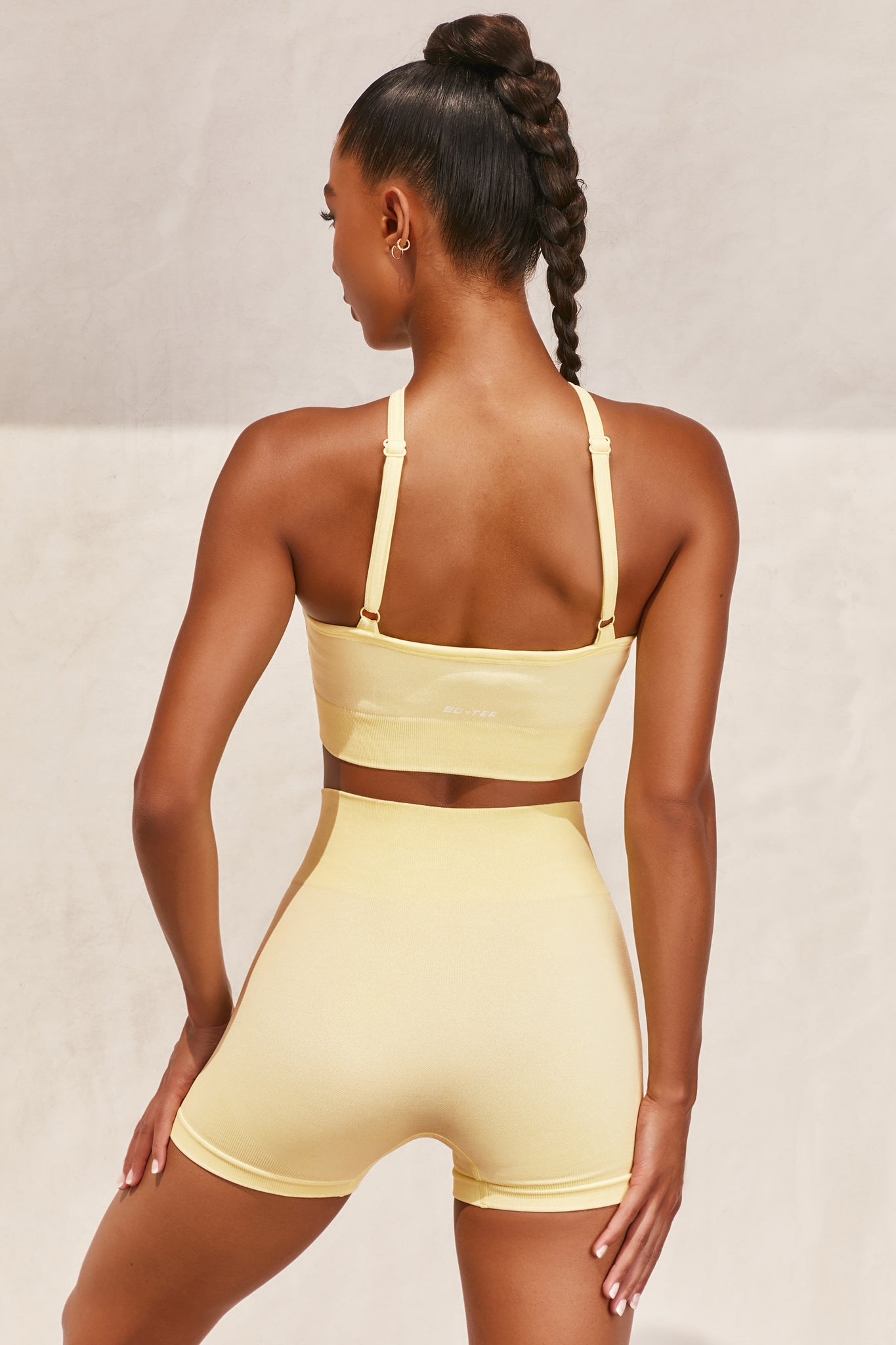 Plain lemon seamless sports bra with cross high-neck adjustable straps and ribbed underband. Image 3 of 6.
