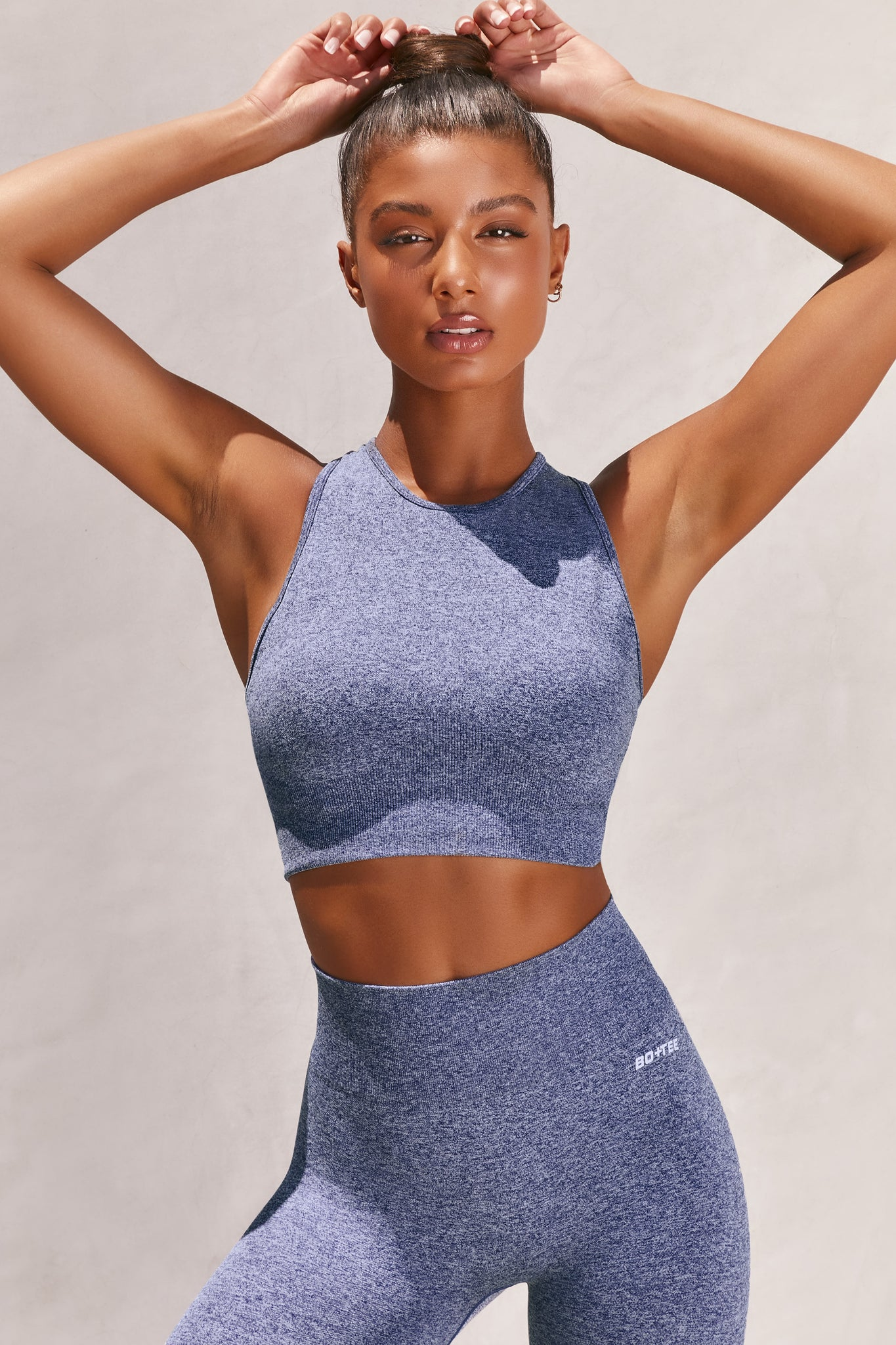 Plain navy marl high neck sleeveless crop top with ribbed underband and racer back. Image 1 of 6.