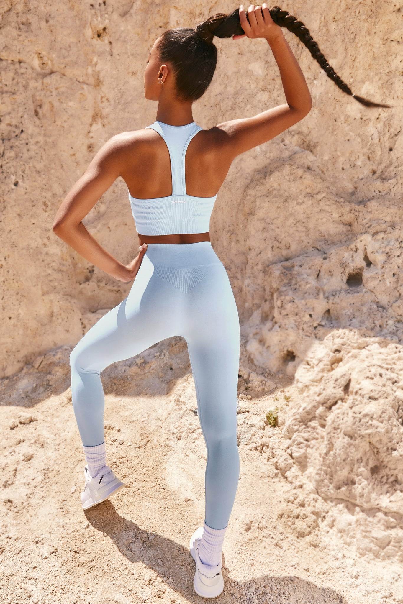 Plain light blue high neck sleeveless crop top with ribbed underband and racer back. Image 3 of 6.
