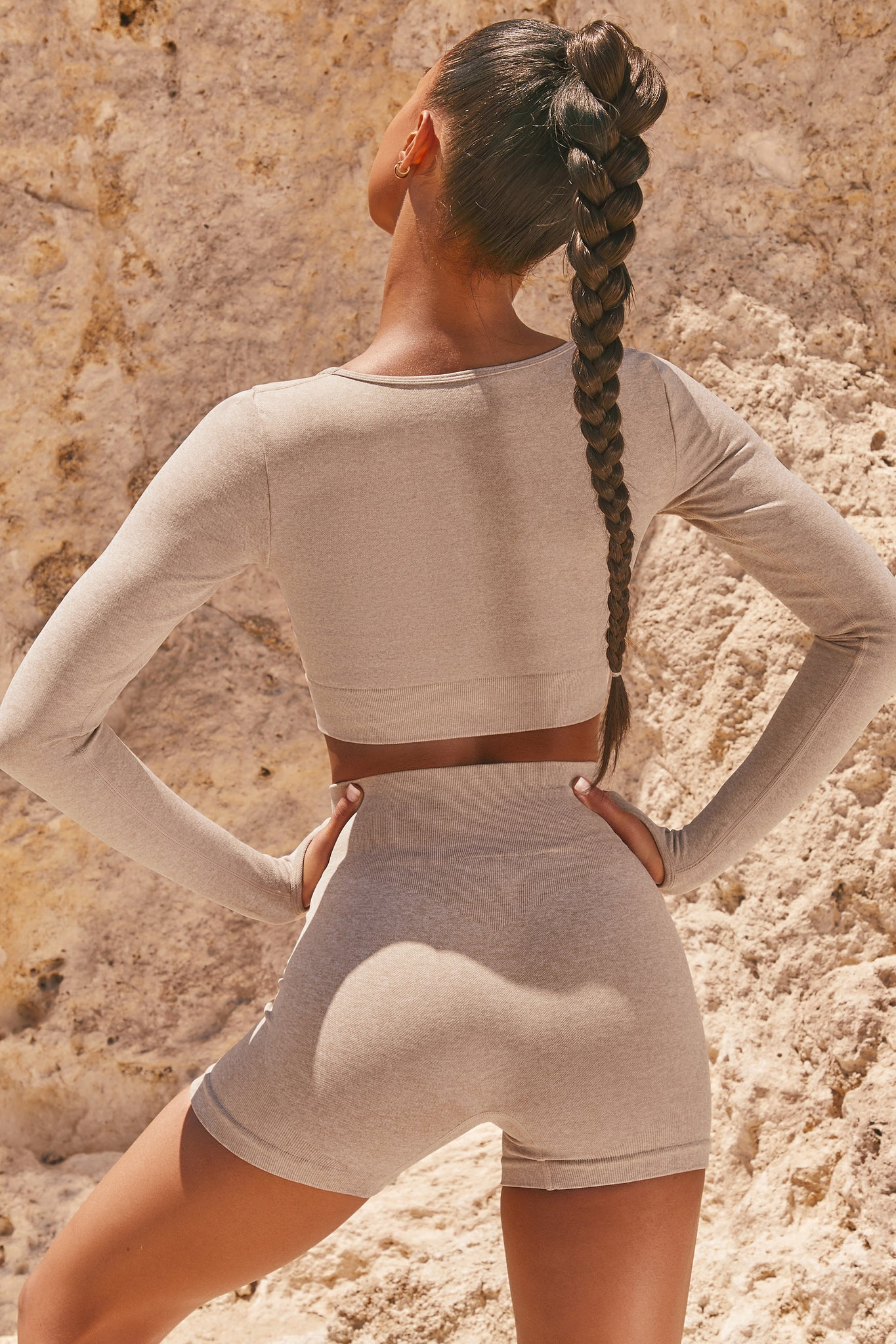 Plain sand seamless long sleeve crop top with low scoop neck and thumb holes. Image 3 of 6.