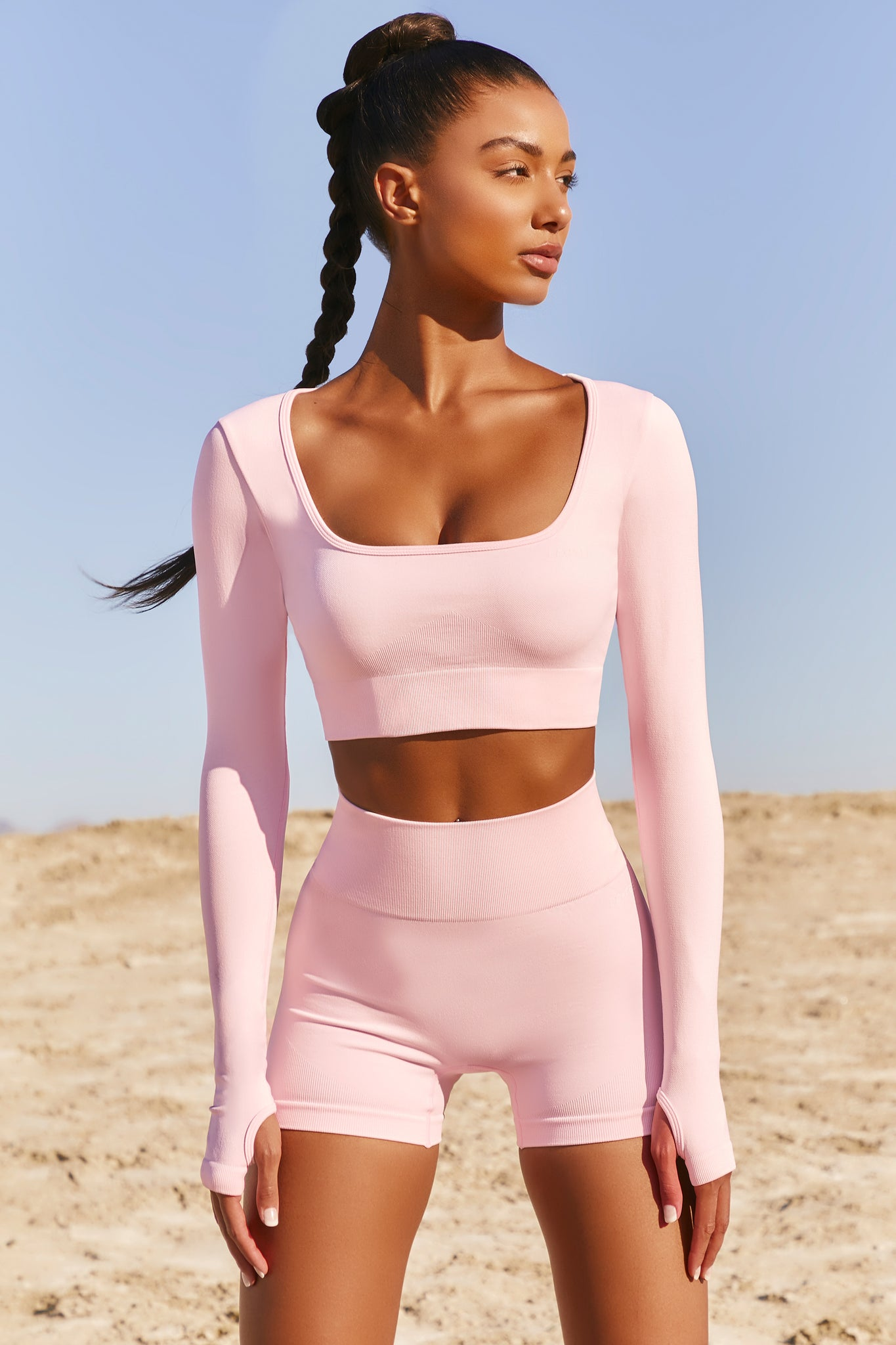 Plain light pink seamless long sleeve crop top with low scoop neck and thumb holes. Image 1 of 6.