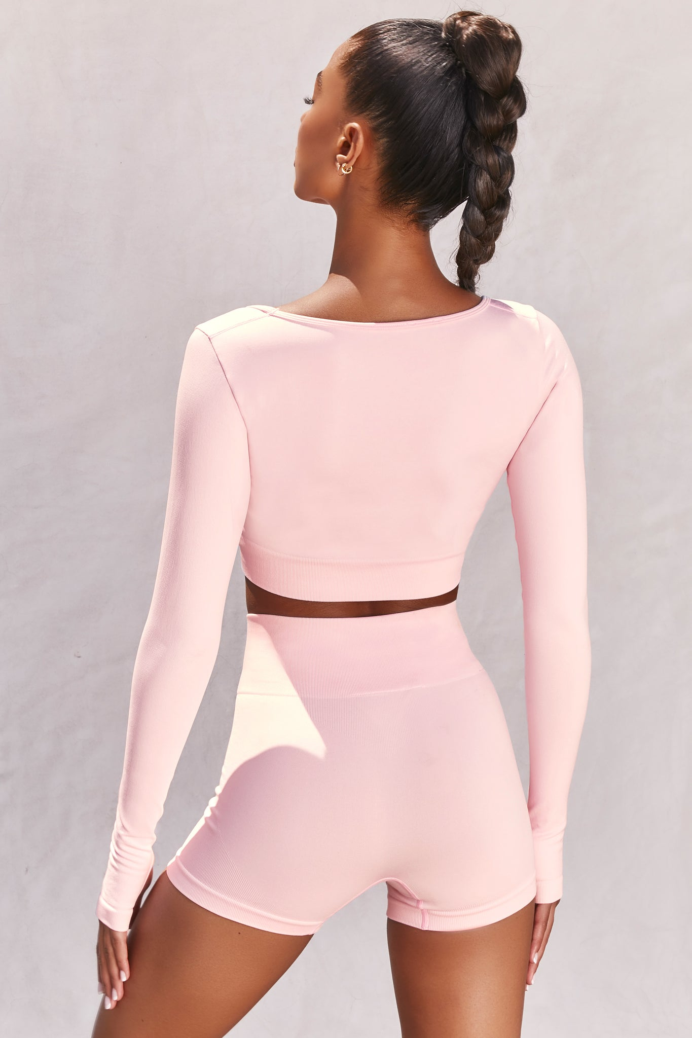 Plain light pink seamless long sleeve crop top with low scoop neck and thumb holes. Image 3 of 6.