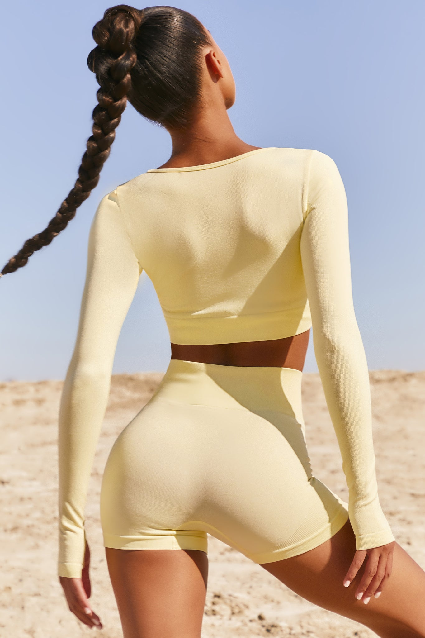 Plain lemon seamless long sleeve crop top with low scoop neck and thumb holes. Image 3 of 6.
