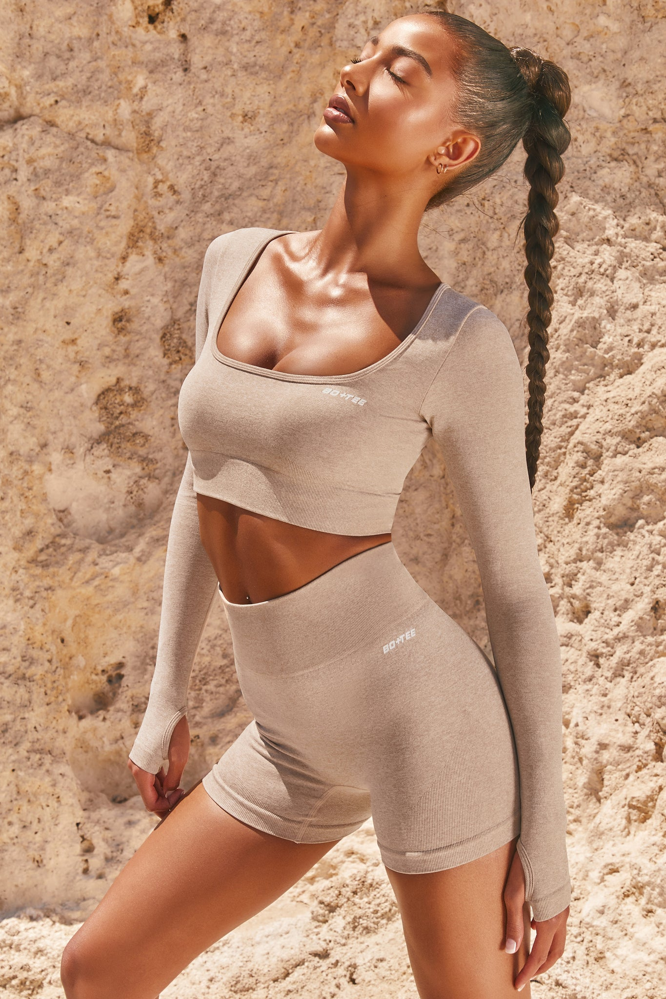 Plain sand seamless long sleeve crop top with low scoop neck and thumb holes. Image 1 of 6.