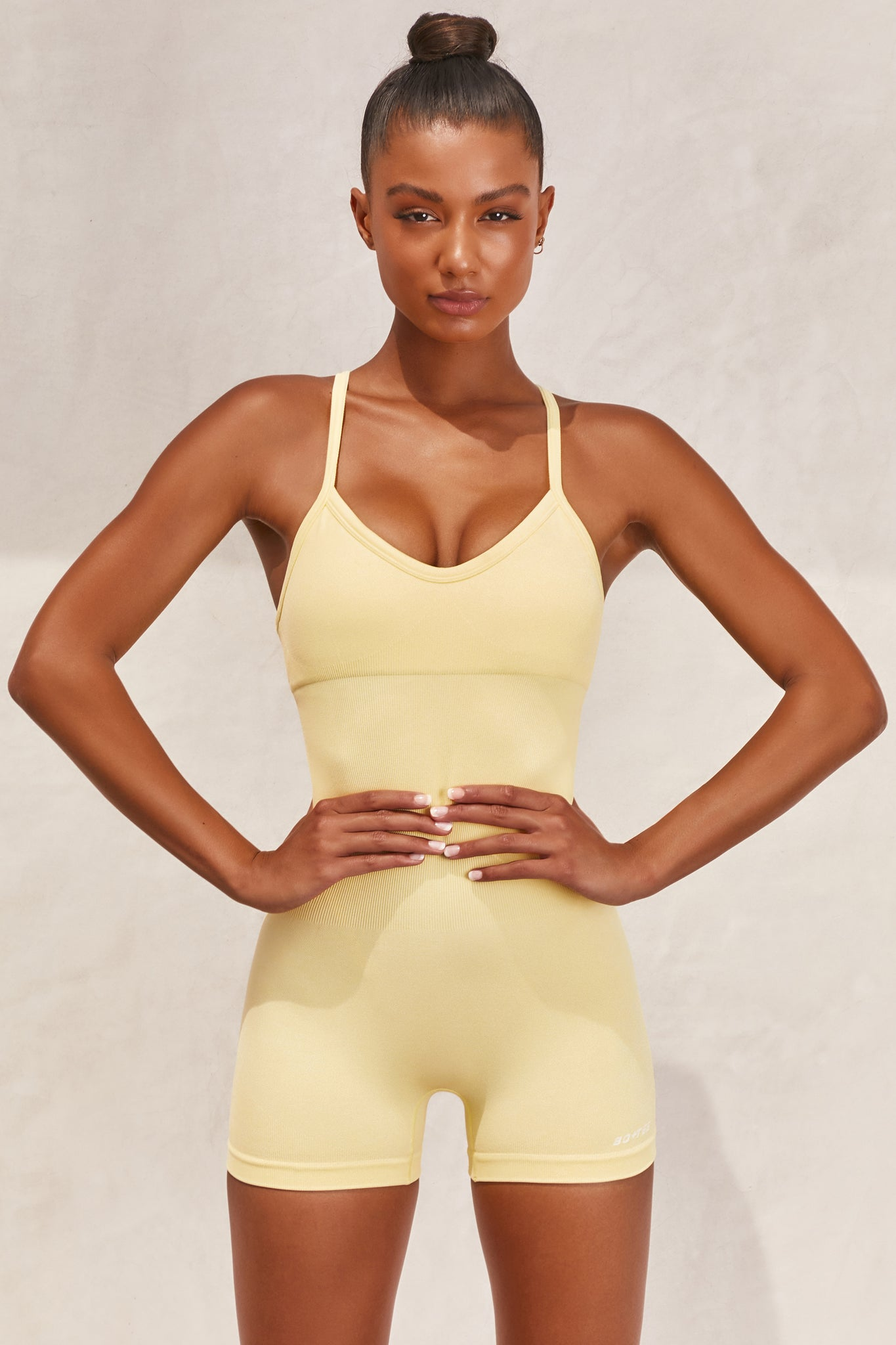 Plain lemon seamless unitard with plunge neck and adjustable straps. Image 1 of 6.
