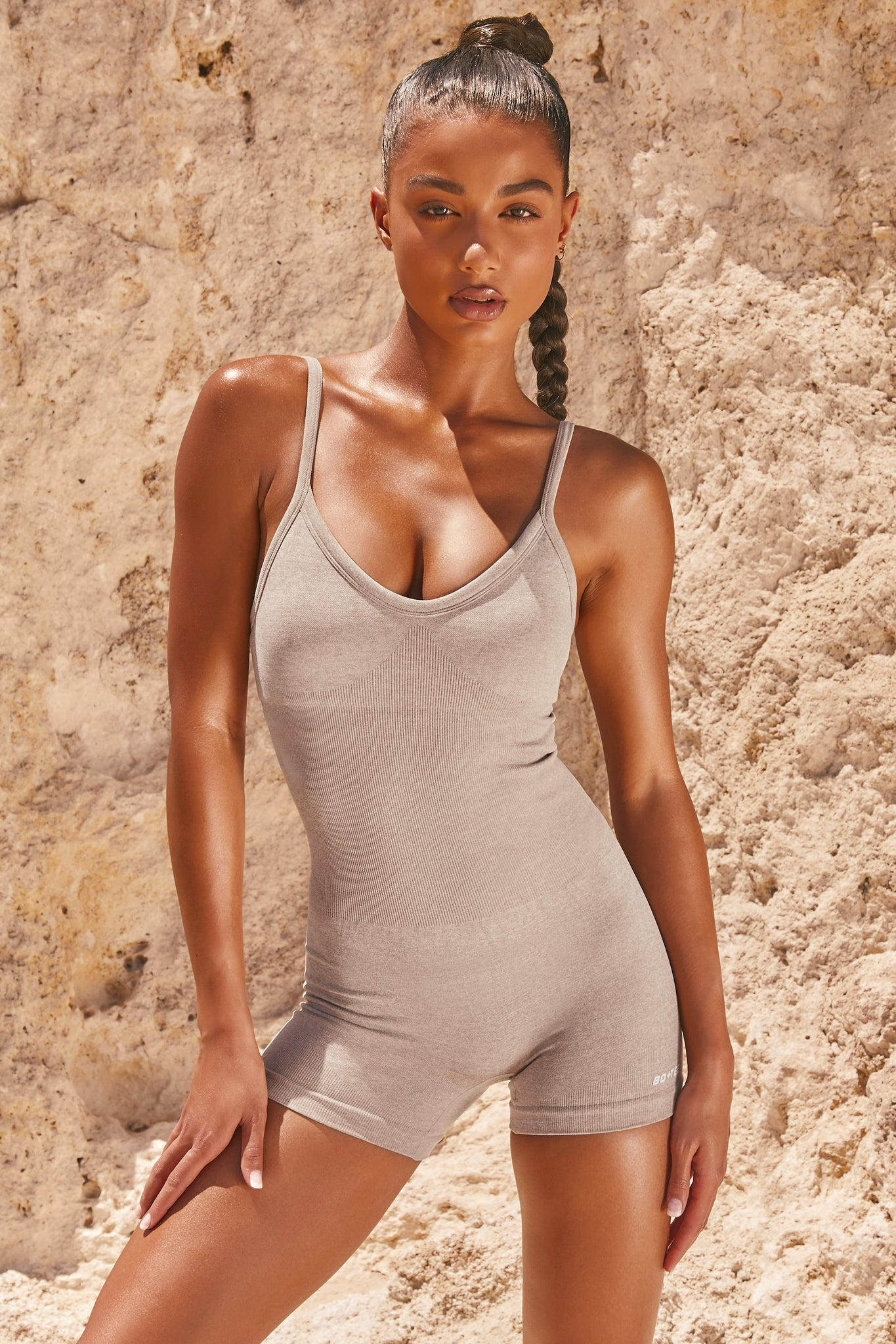 Plain sand seamless unitard with plunge neck and adjustable straps. Image 1 of 6.