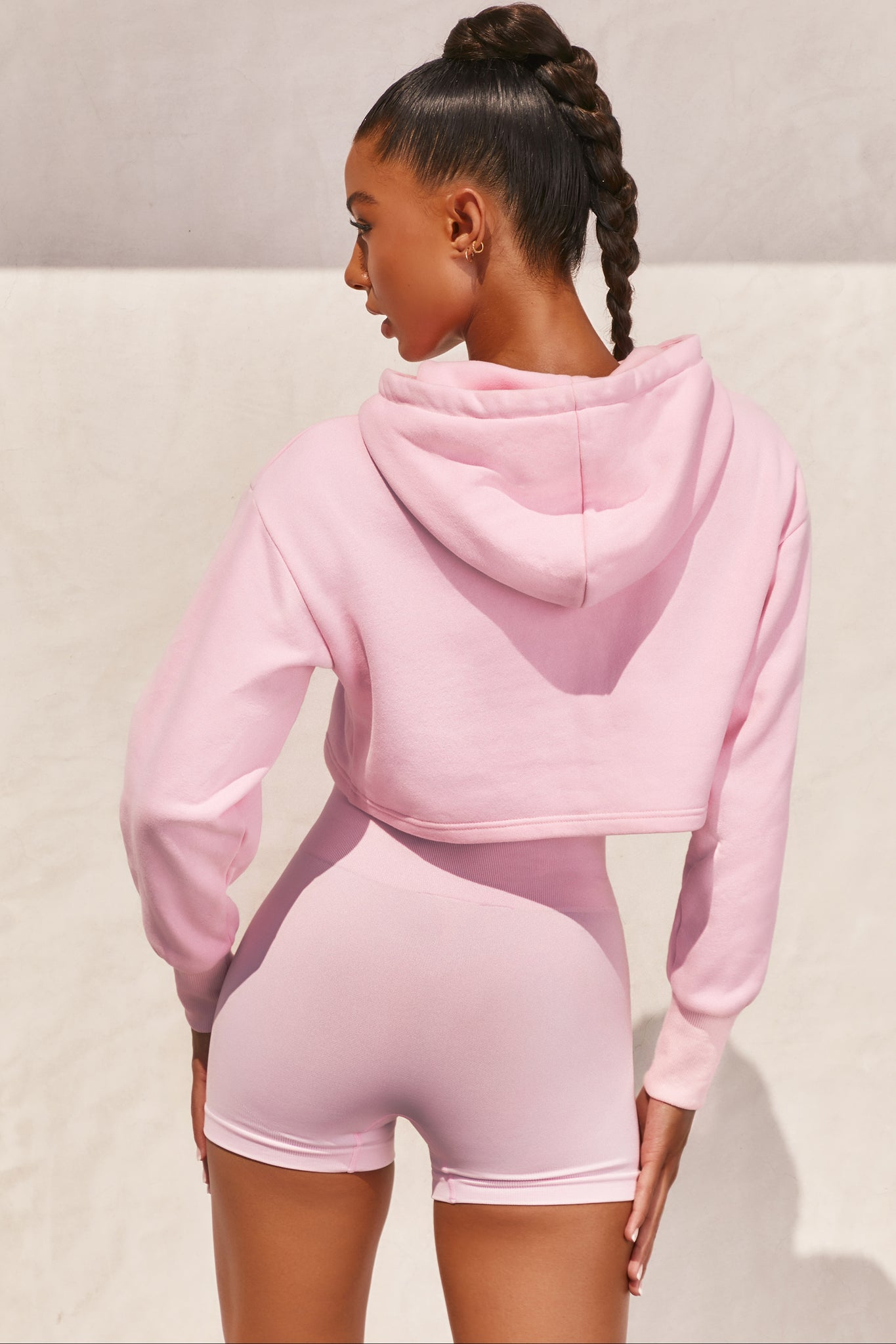 Pink long sleeved hoodie with embroidered Bo+Tee logo across the chest. Image 3 of 6