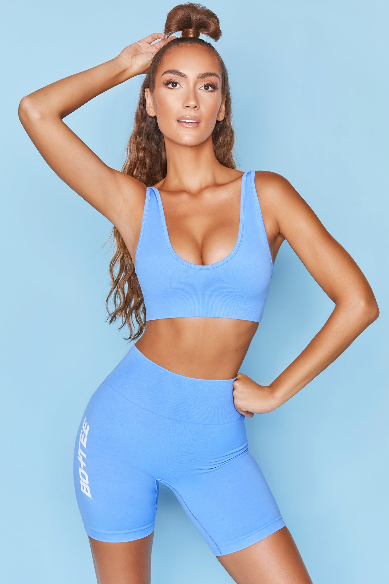 Bright blue plunge neck sports bra with ribbed underband. Image 6 of 6.
