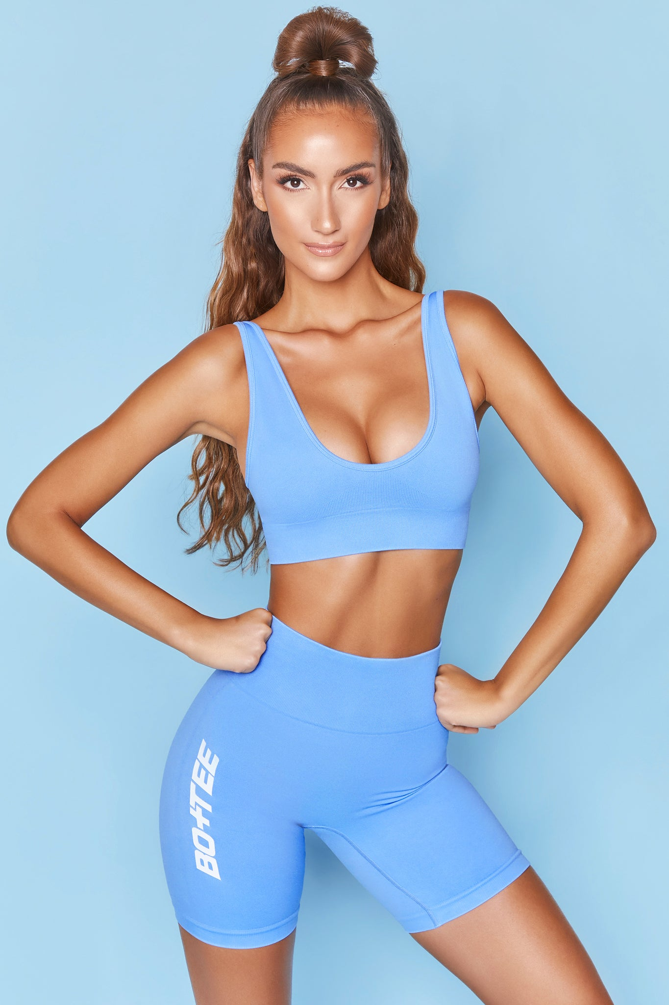 Bright blue plunge neck sports bra with ribbed underband. Image 1 of 6.