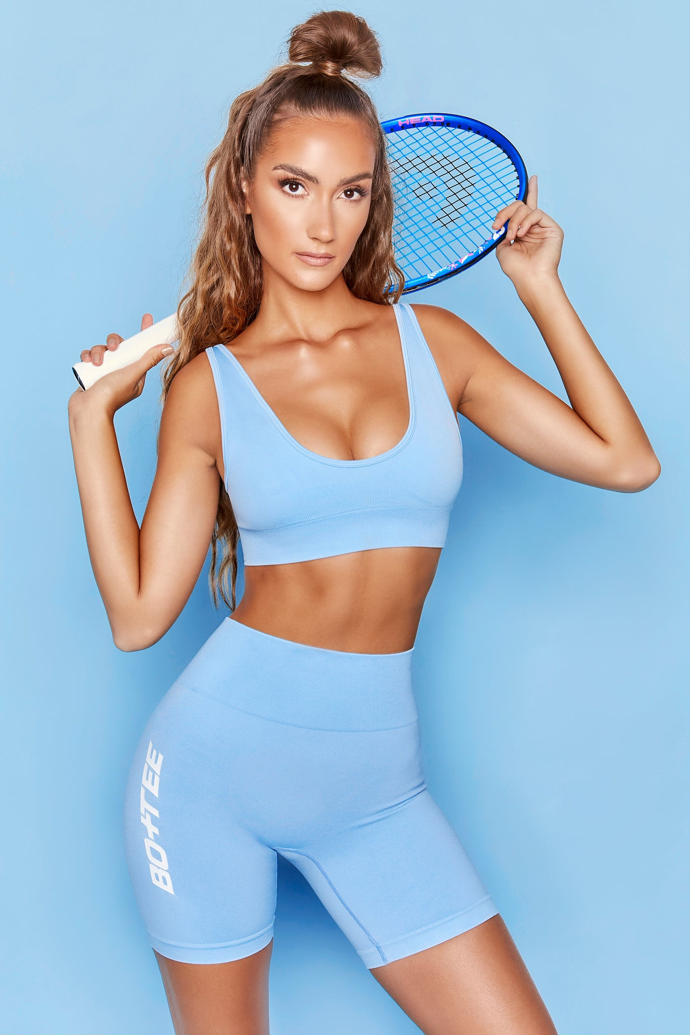 Light blue high waisted mid thigh length cycling shorts with Bo+Tee branding down the leg. Image 1 of 6.
