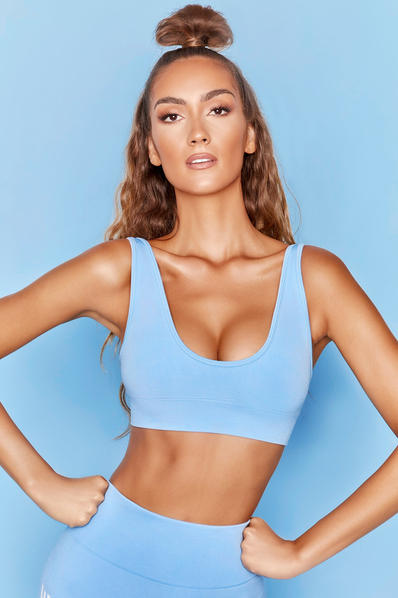Light blue plunge neck sports bra with ribbed underband. Image 5 of 6.