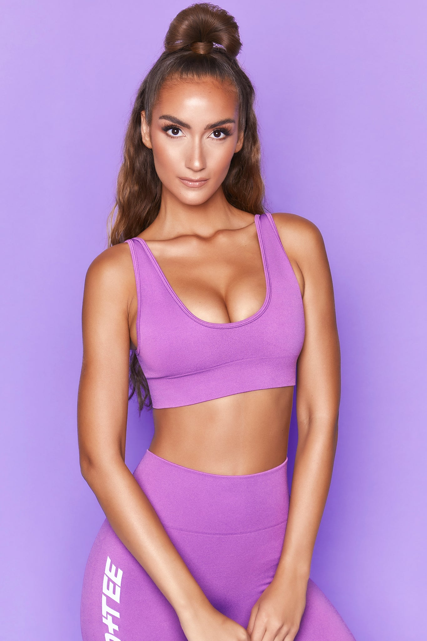 Purple plunge neck sports bra with ribbed underband and adjustable straps. Image 1 of 6.