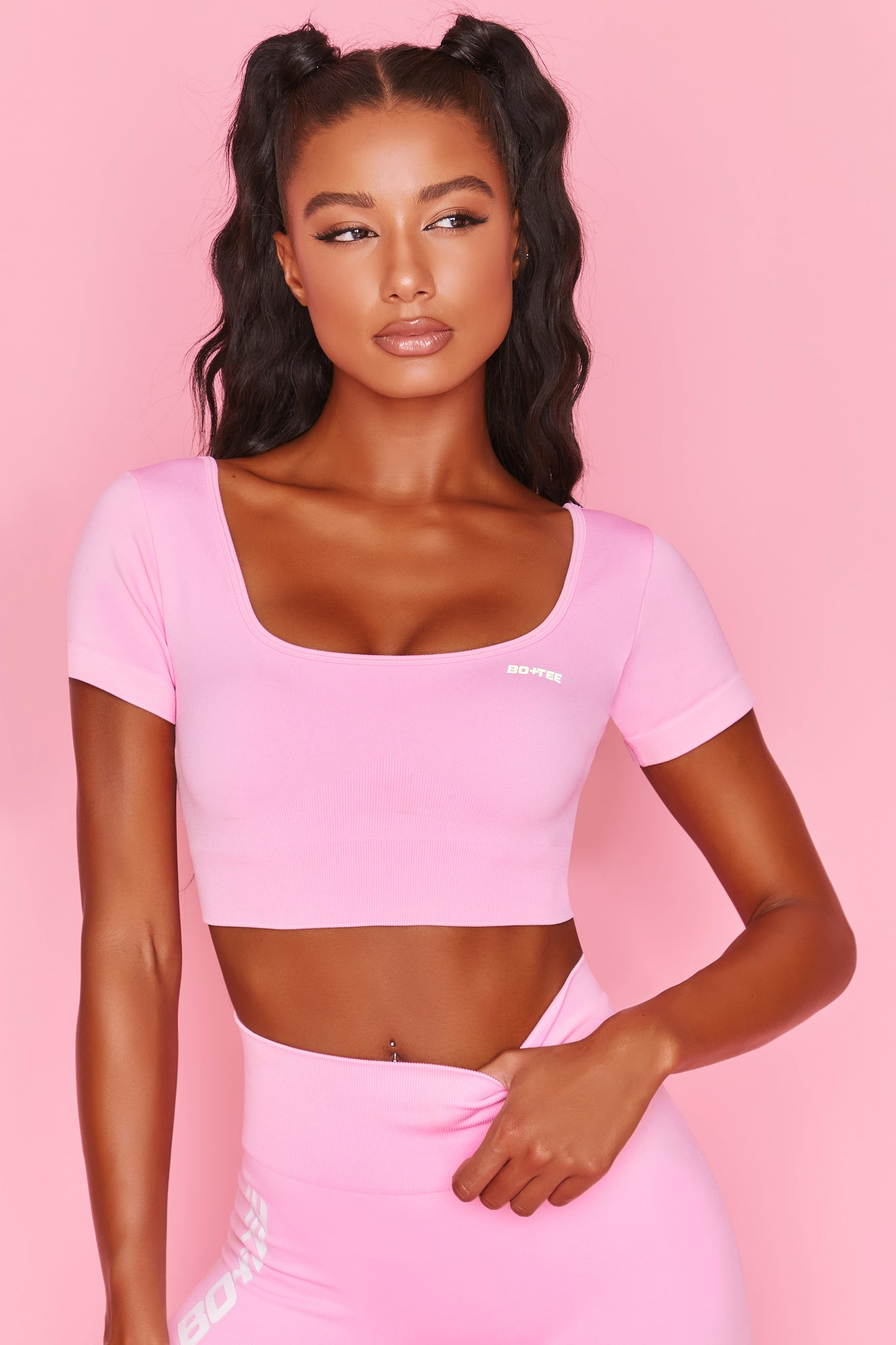 Pink scoop neck crop top with short sleeves and ribbed underband. Image 1 of 6.