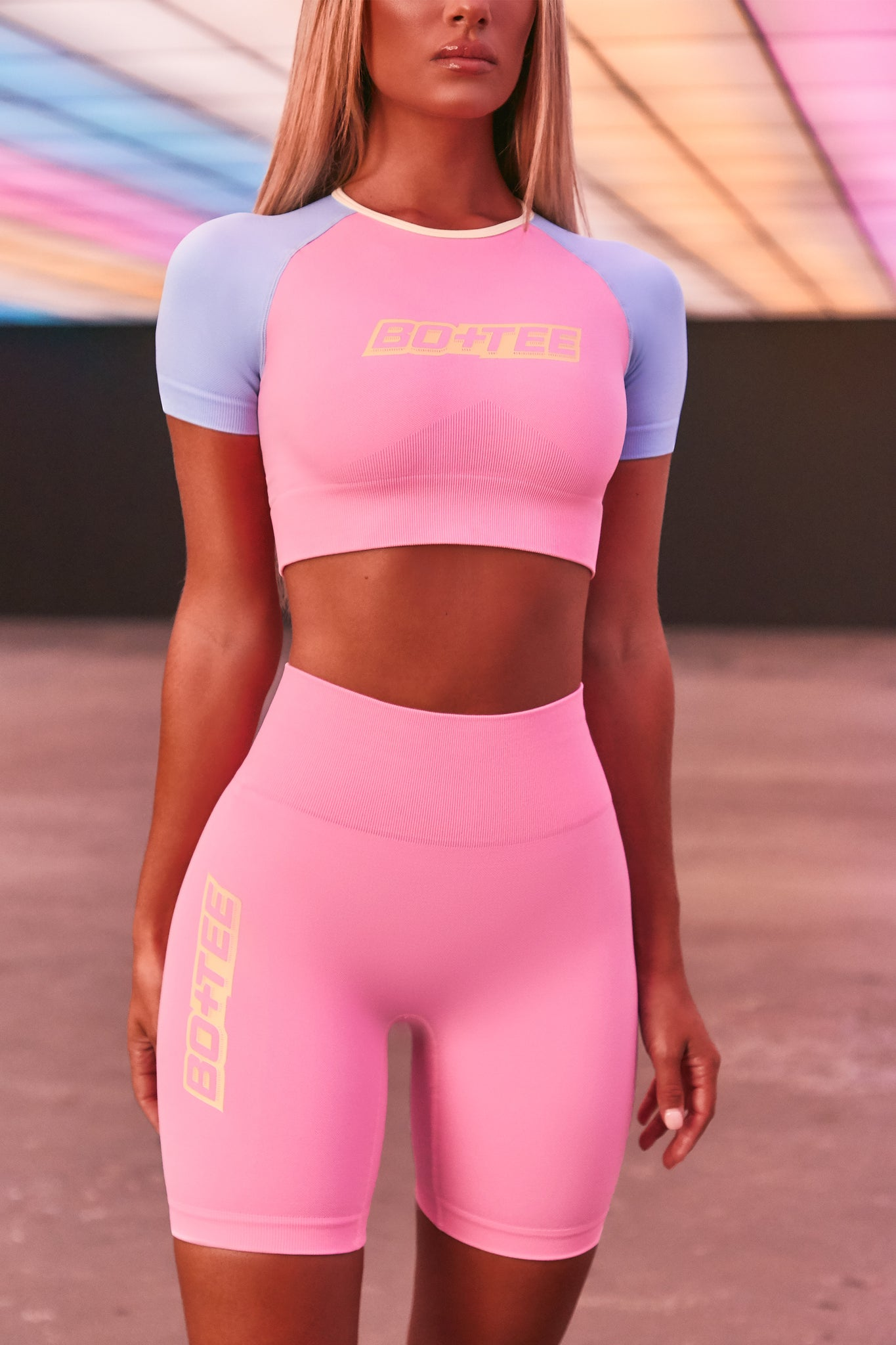 Pink seamless high waisted cycling shorts with 3D branding down the leg. Image 5 of 6.