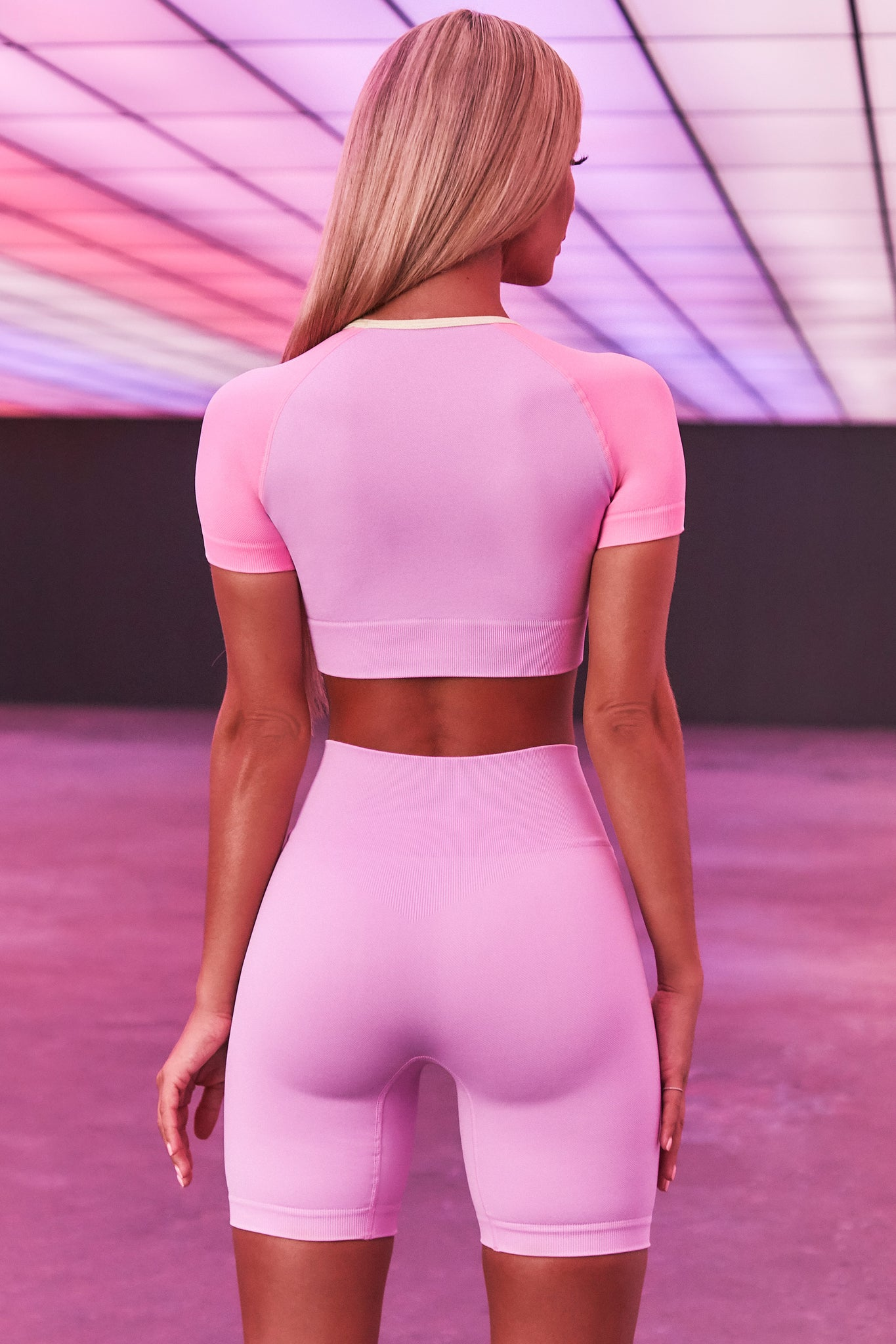 Lilac seamless short sleeve crop top with pink sleeves and 3D branding across the chest. Image 3 of 6.