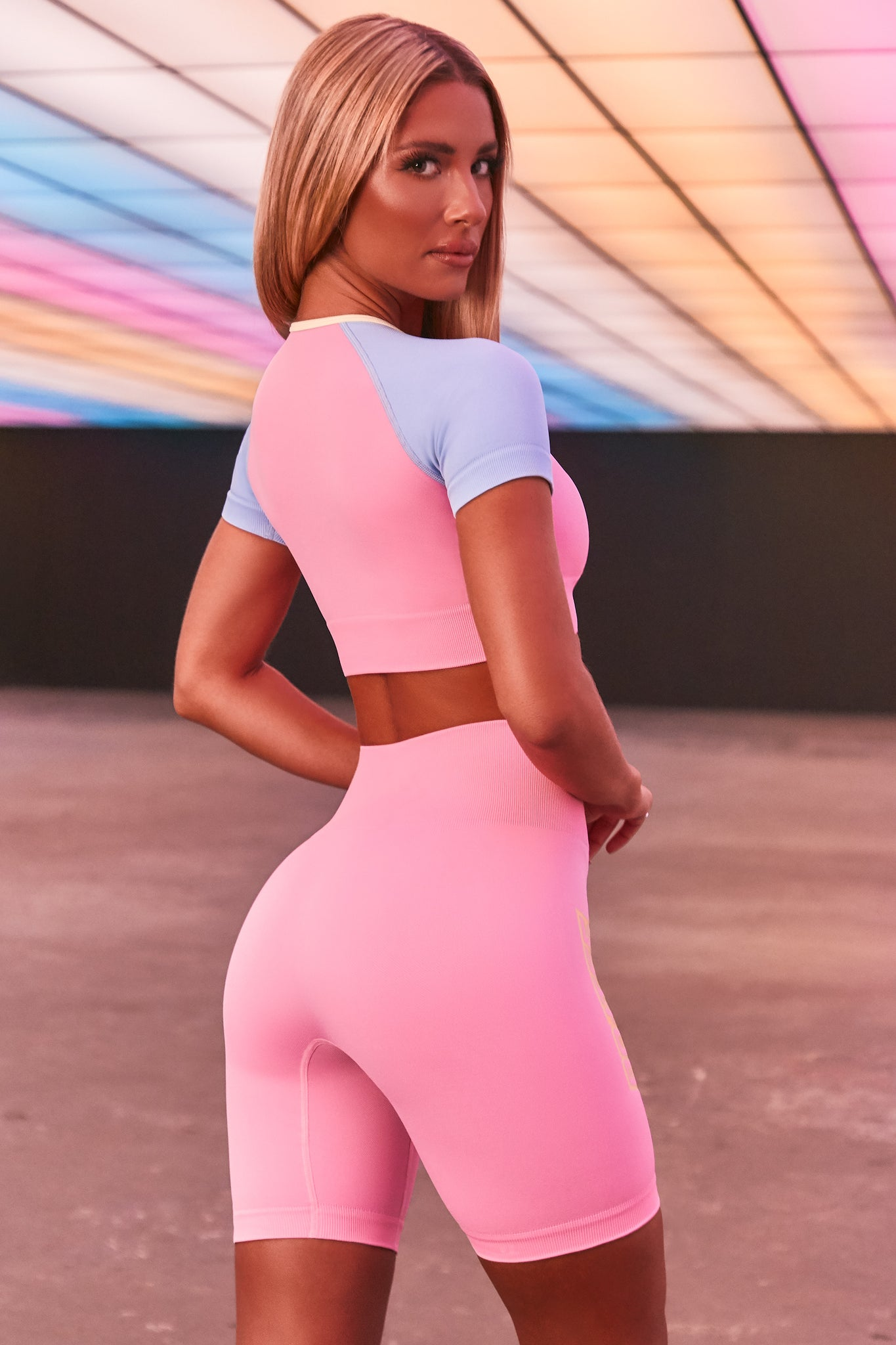 Pink seamless high waisted cycling shorts with 3D branding down the leg. Image 3 of 6.