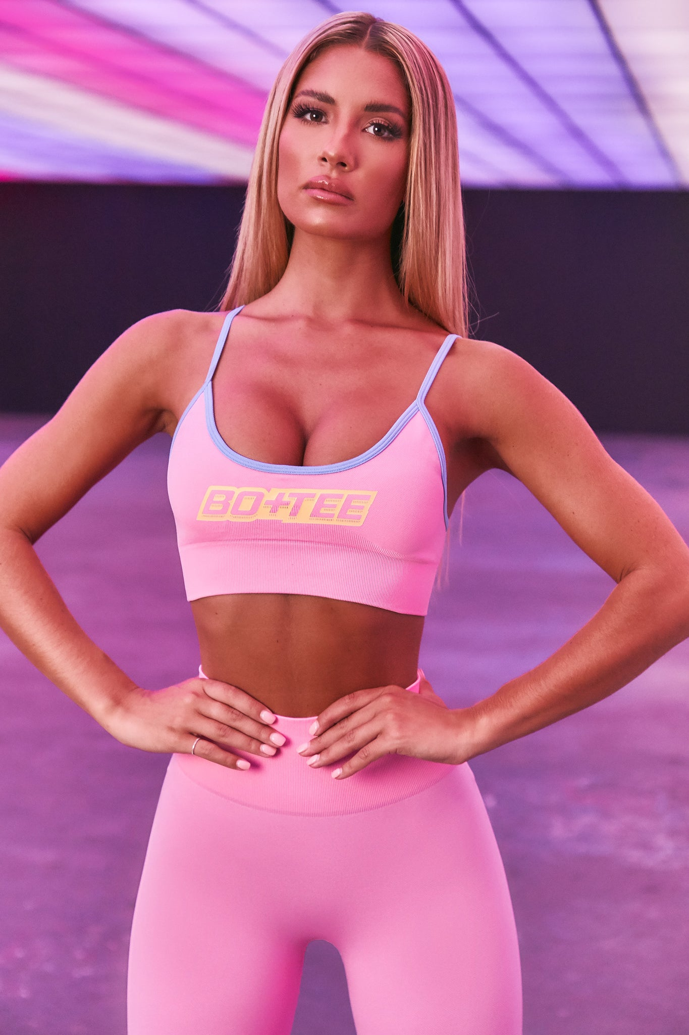 Pink seamless sports bra with scoop neckline and contrasting blue straps. 3D branding across the chest. Image 1 of 6.