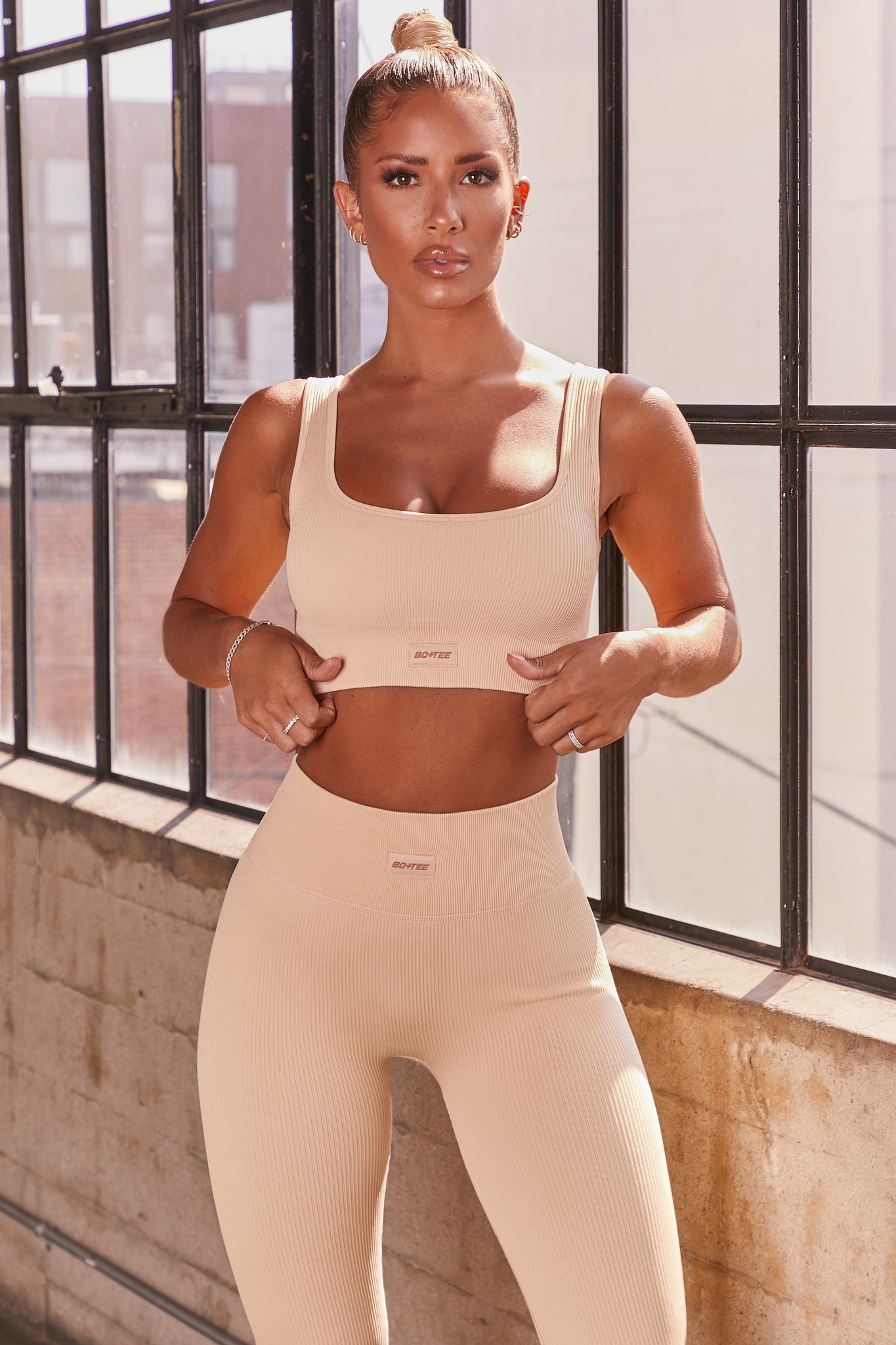 Cream ribbed scoop neck sports bra. Image 1 of 6.