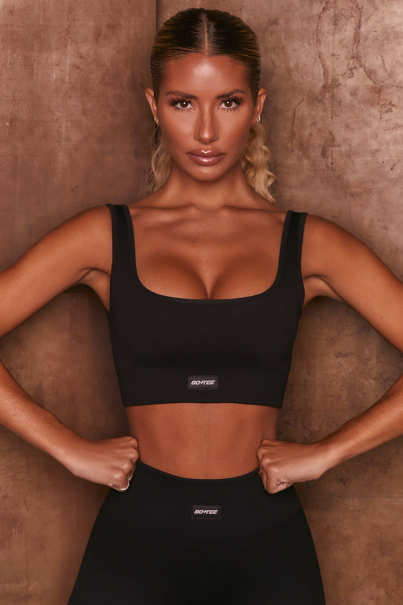 Black ribbed scoop neck sports bra. Image 1 of 6.