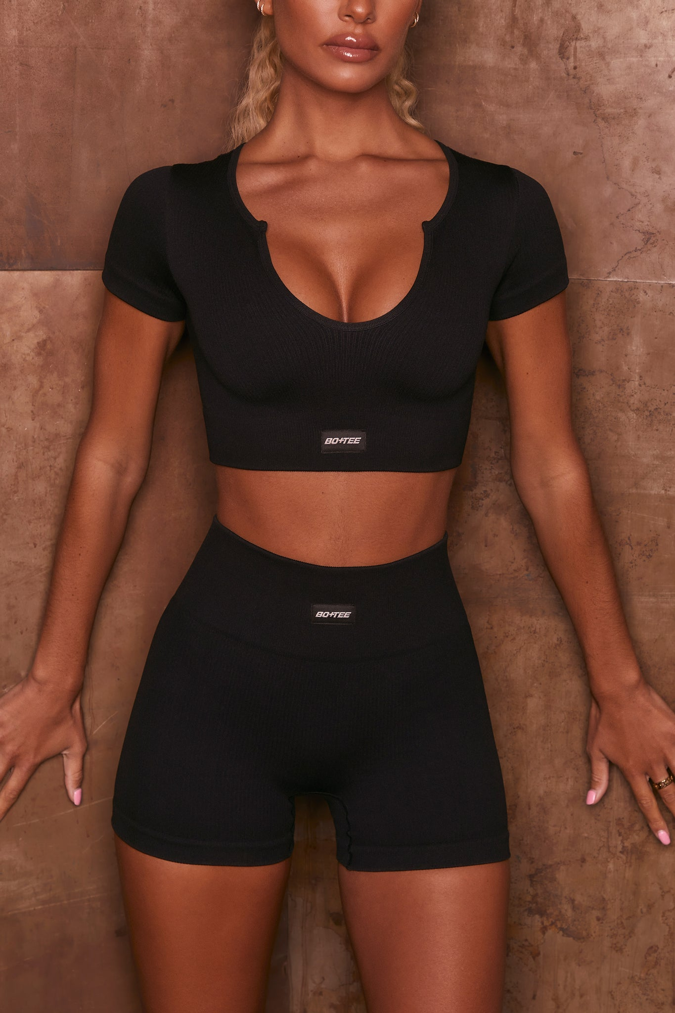 Black ribbed high waisted mini gym shorts. Image 4 of 6.
