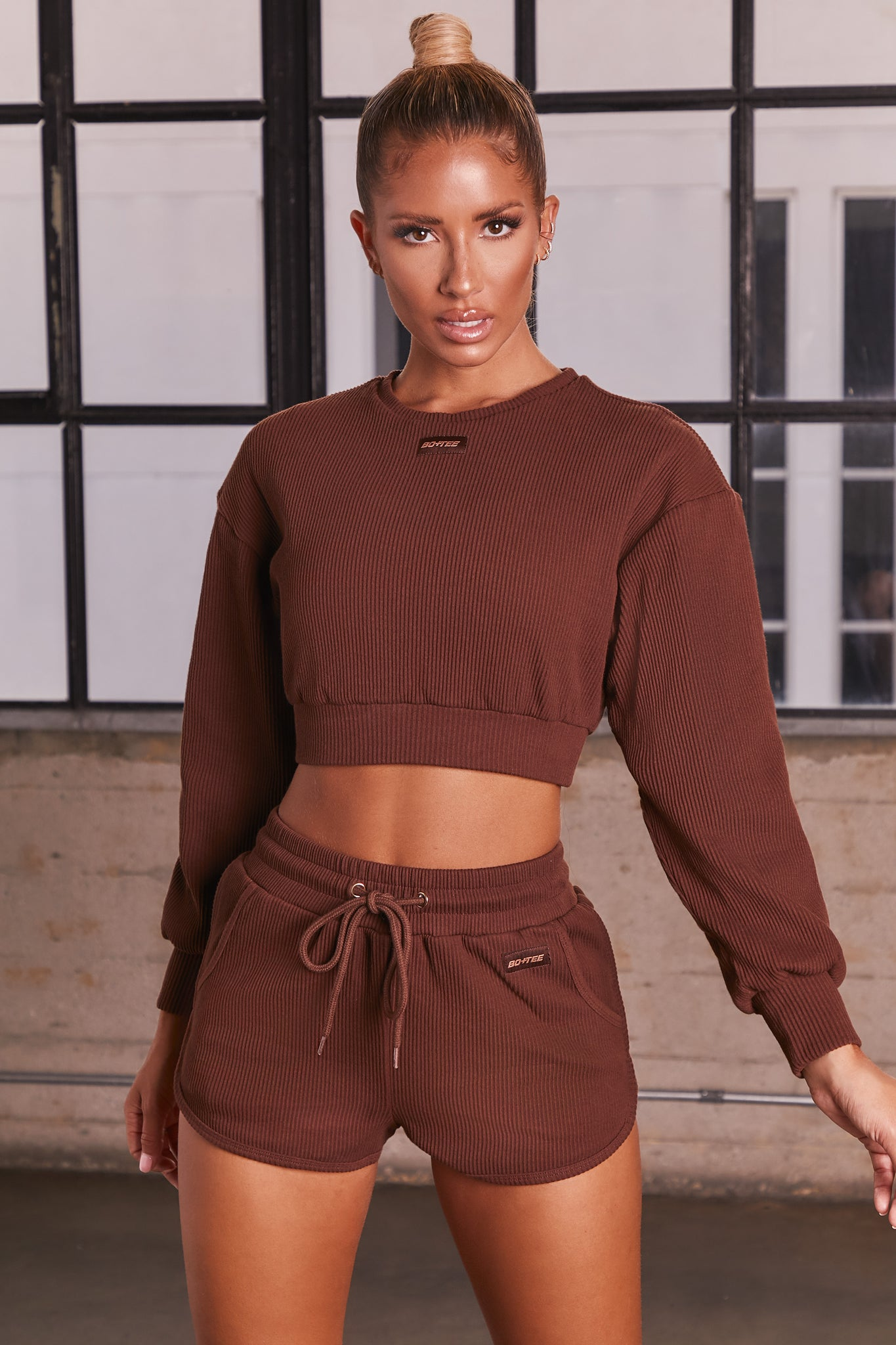 Dark Brown ribbed high waisted mini runner shorts. Image 1 of 6.