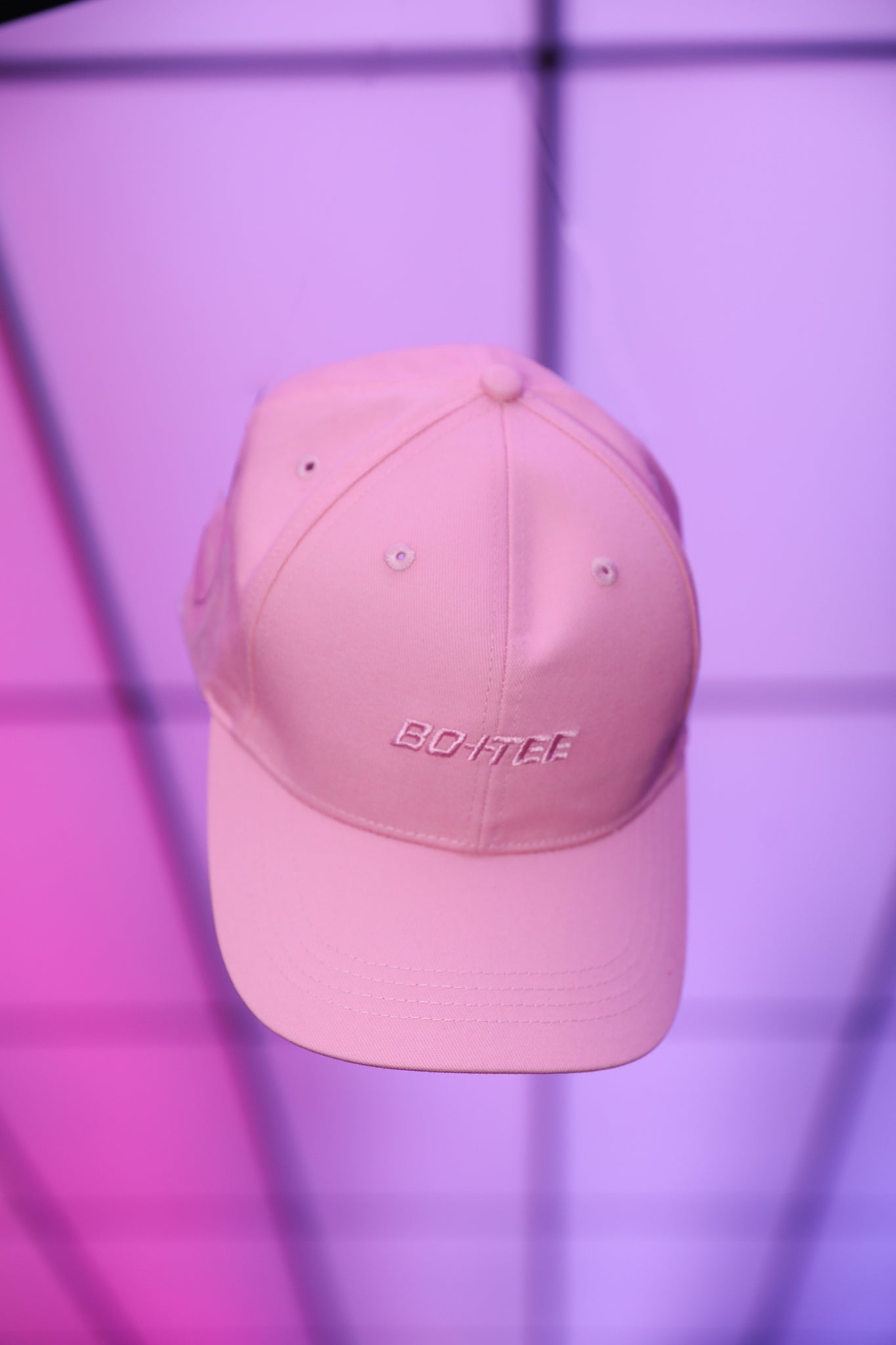 Pink baseball cap with embroidered logo in the centre. Image 3 of 6.